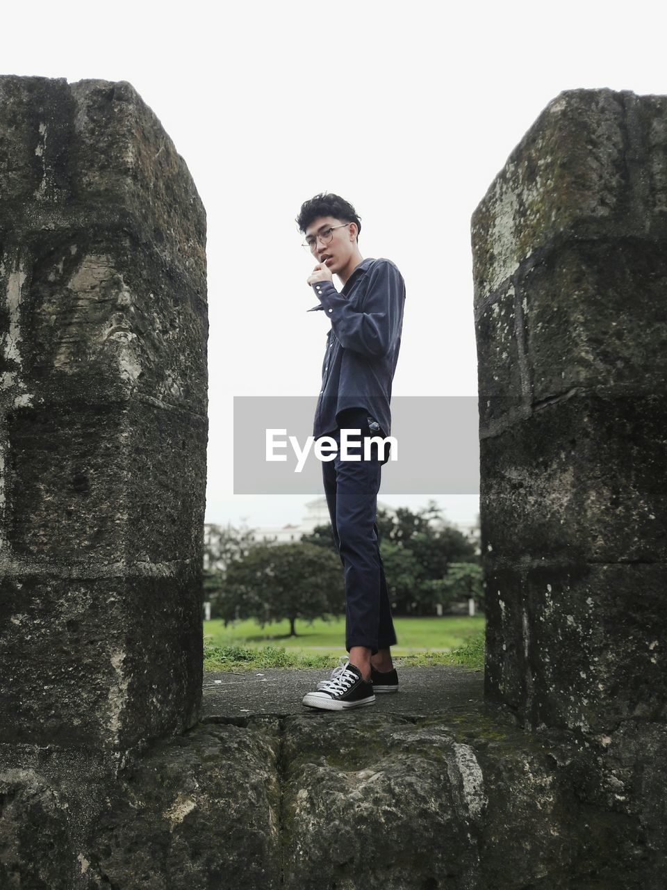 Young Man Standing Amidst Retaining Wall Against Sky