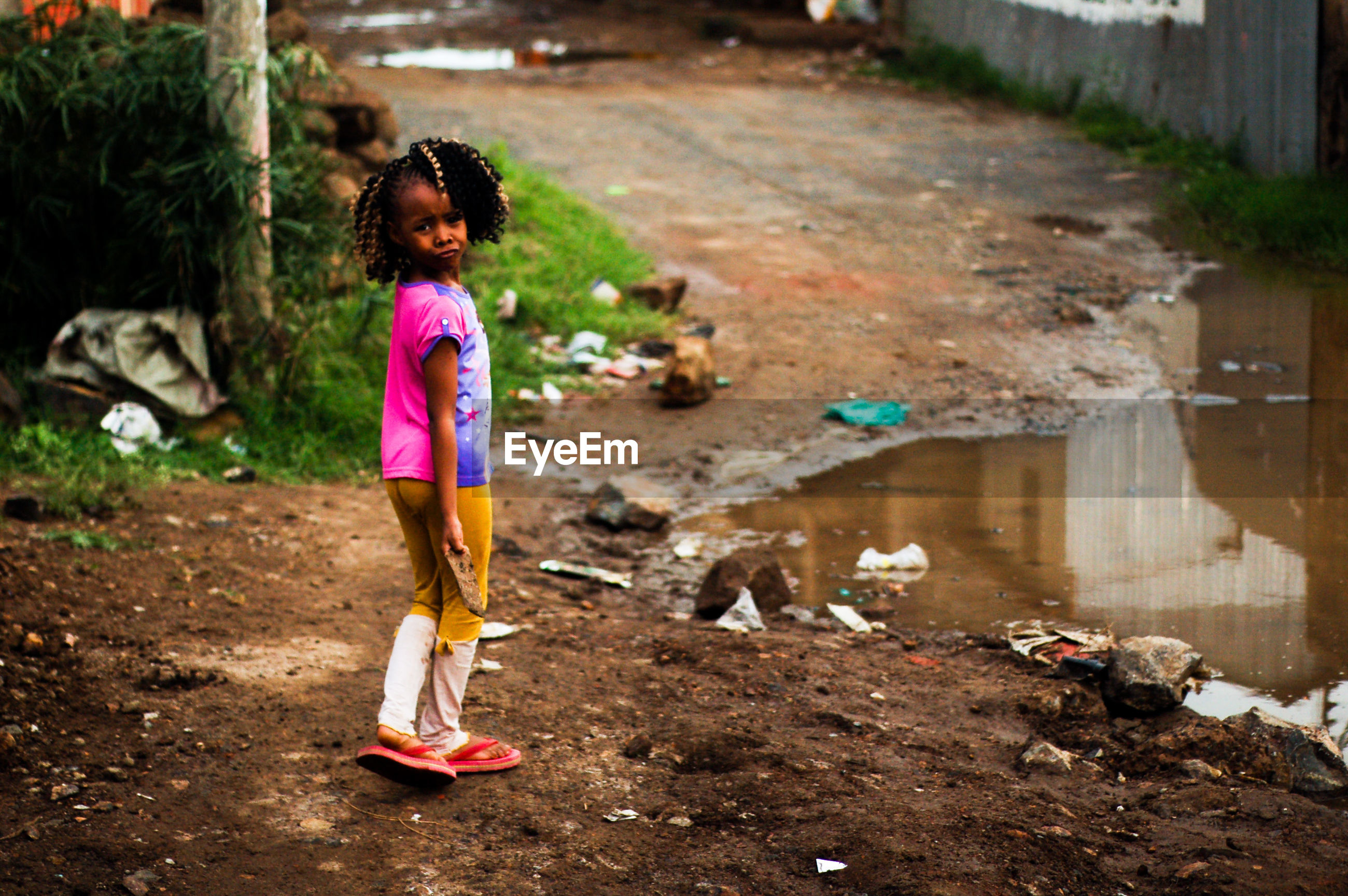 Girl standing by puddle on pathway
