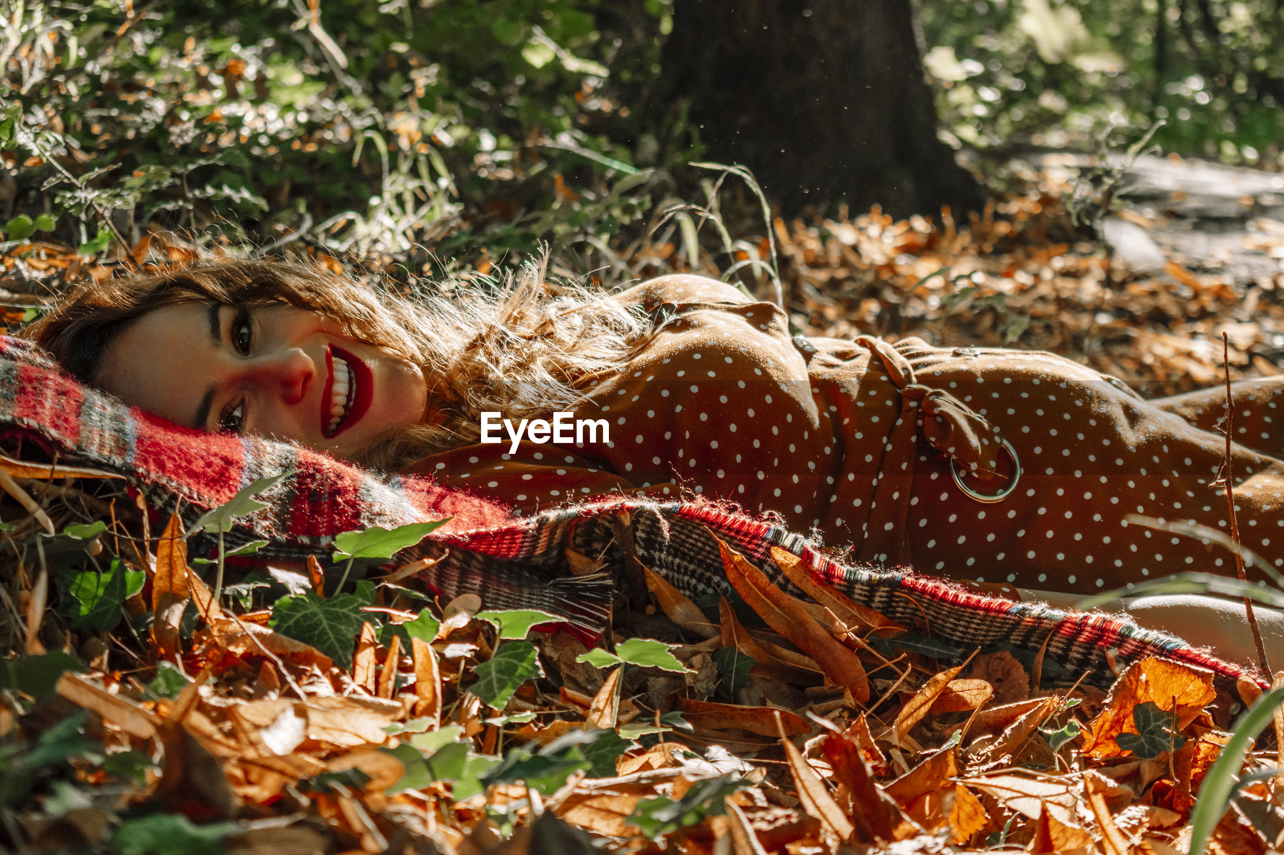 Portrait of smiling woman lying down at forest