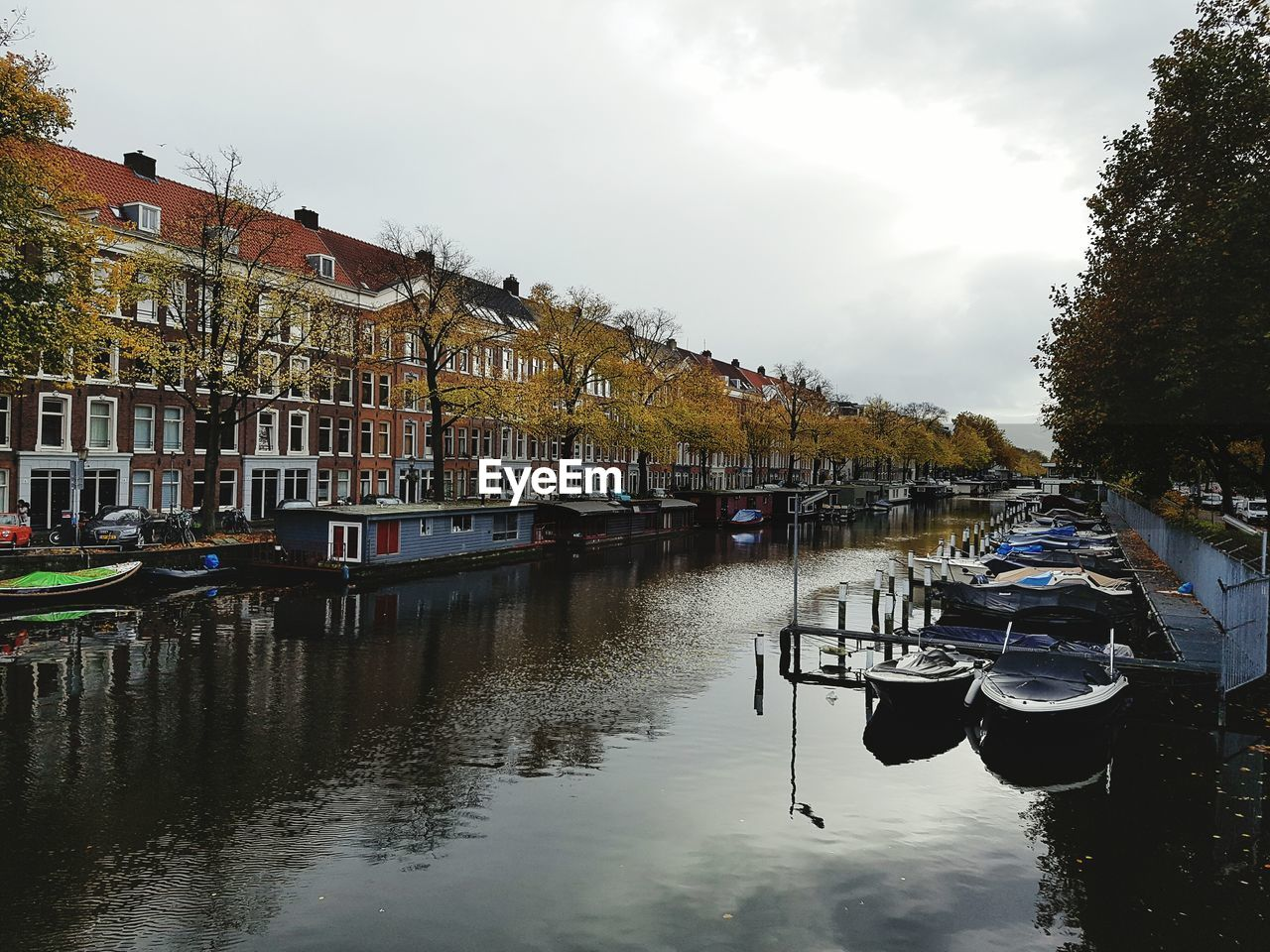 nautical vessel, moored, mode of transport, transportation, boat, sky, water, in a row, canal, reflection, outdoors, day, no people, tree, architecture, built structure, building exterior, harbor, nature