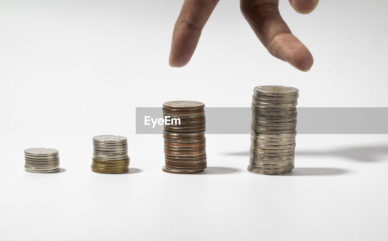 CROPPED IMAGE OF HAND HOLDING STACK OF COINS