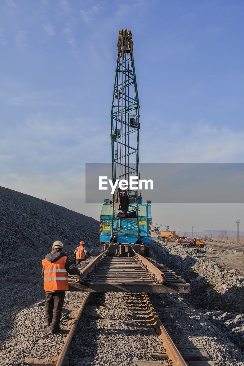 construction site, industry, machinery, construction machinery, technology, occupation, real people, sky, day, men, working, outdoors, one person, progress, construction worker, wireless technology, manual worker, hardhat, architecture, reflective clothing, drilling rig, people