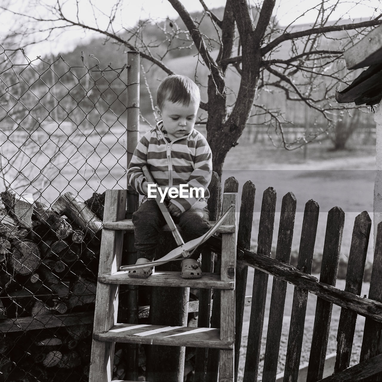 BOY STANDING BY FENCE AND TREE IN WINTER