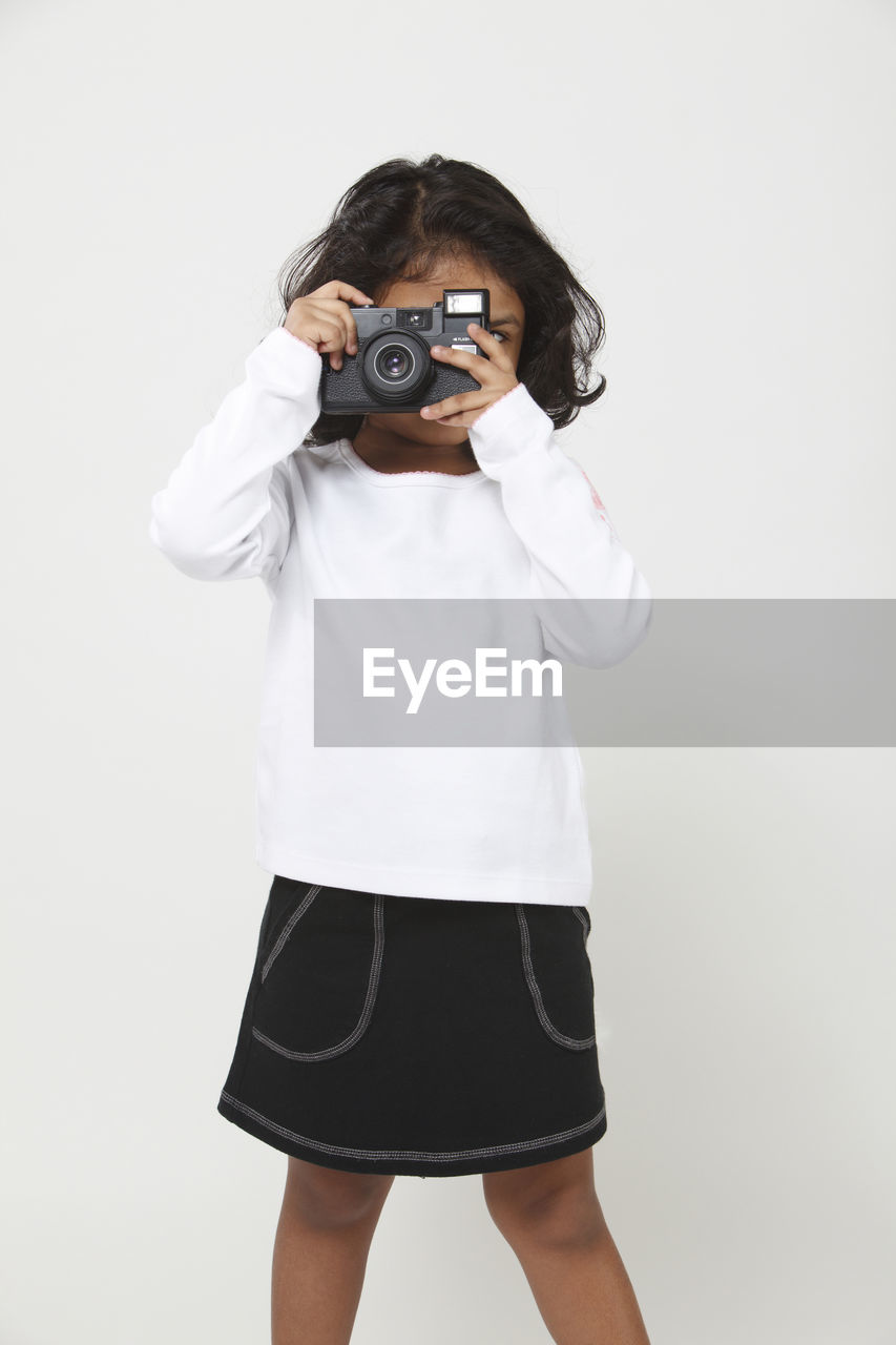 studio shot, one person, white background, photography themes, standing, indoors, camera - photographic equipment, photographing, cut out, holding, front view, technology, casual clothing, three quarter length, childhood, child, real people, lifestyles, leisure activity, digital camera, photographer, shorts, obscured face