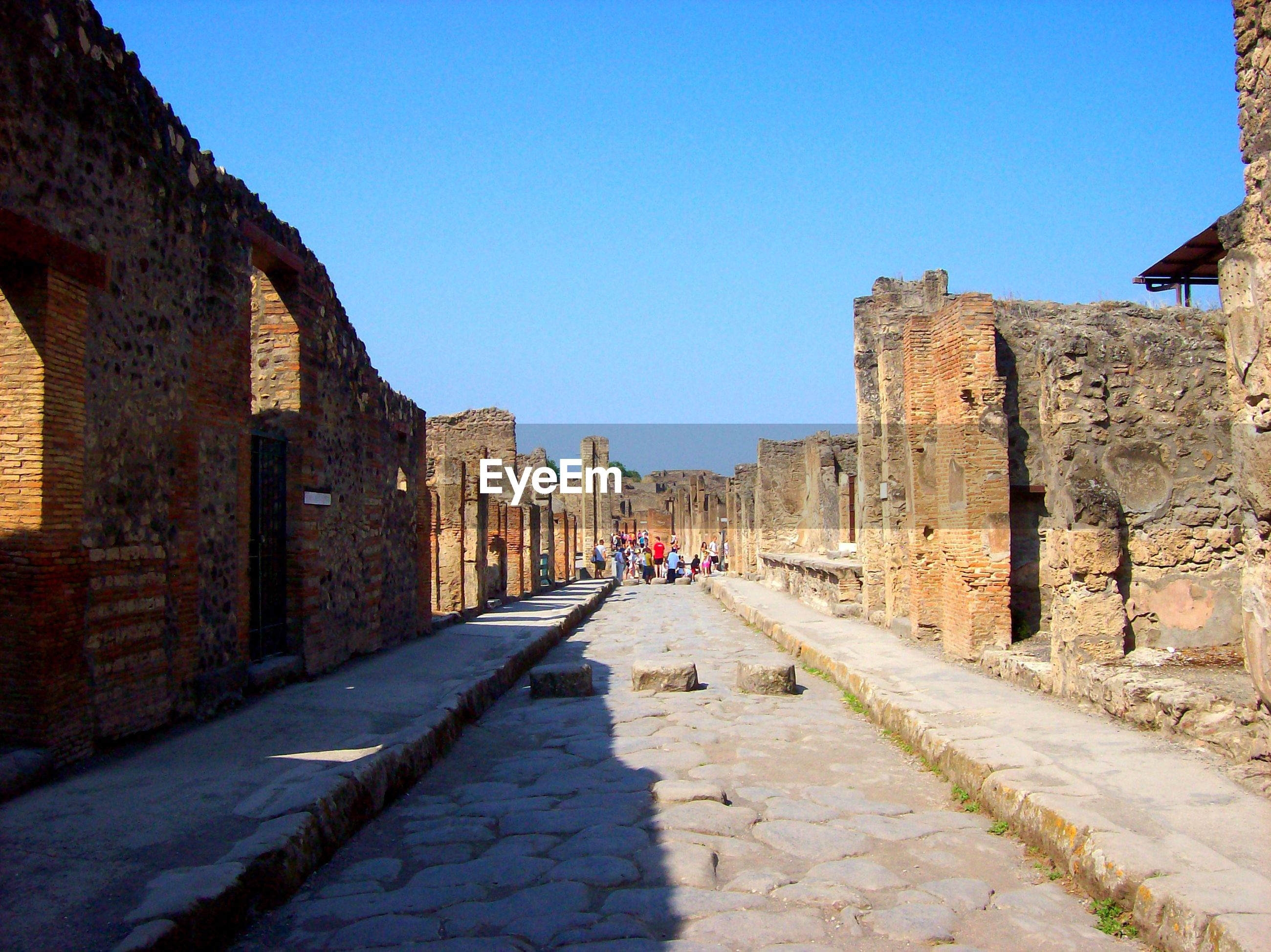 architecture, built structure, history, building exterior, ancient, clear sky, old ruin, real people, ancient civilization, day, sunlight, shadow, outdoors, travel destinations, men, sky, people