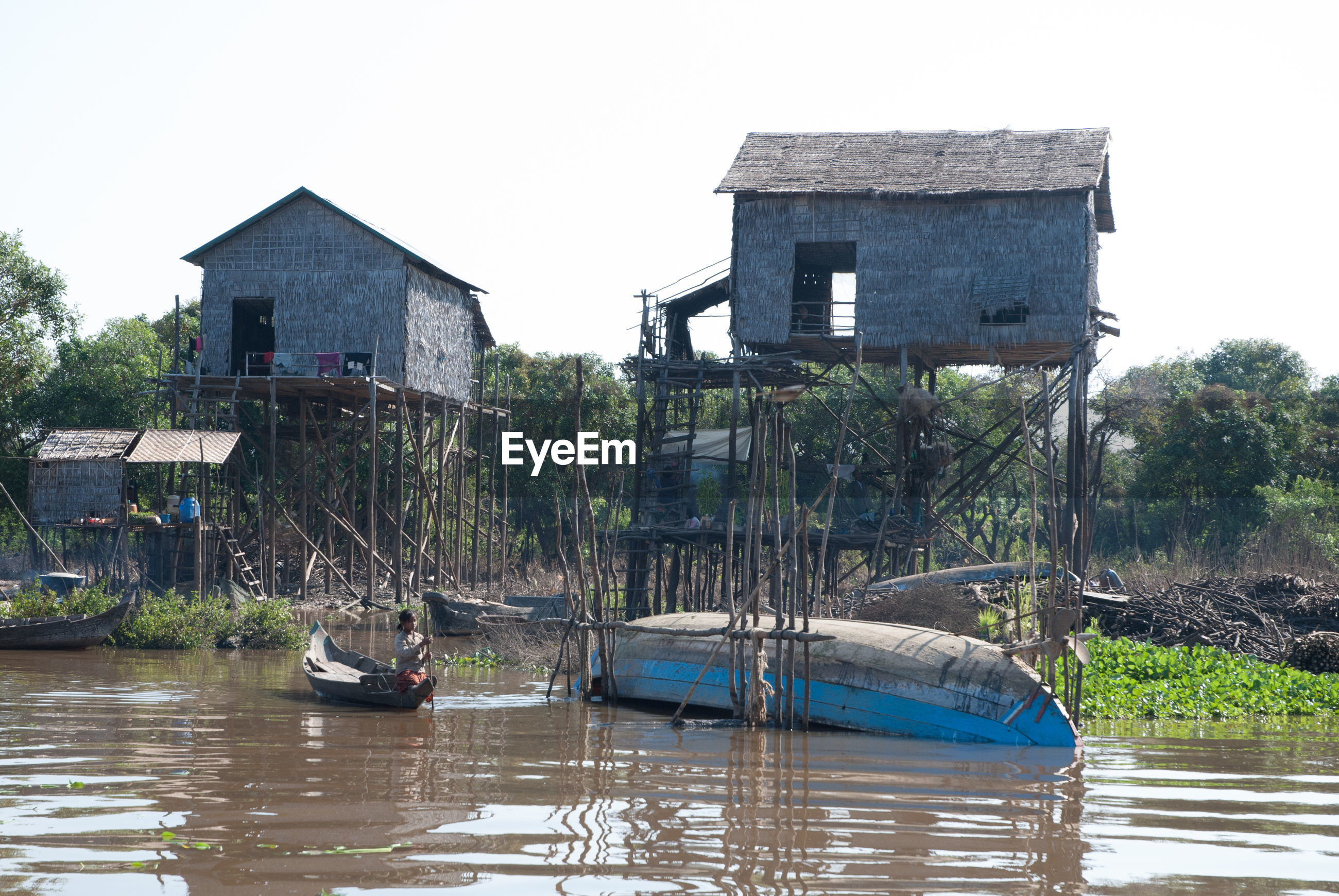 BOATS MOORED IN RIVER WITH BUILDINGS IN BACKGROUND