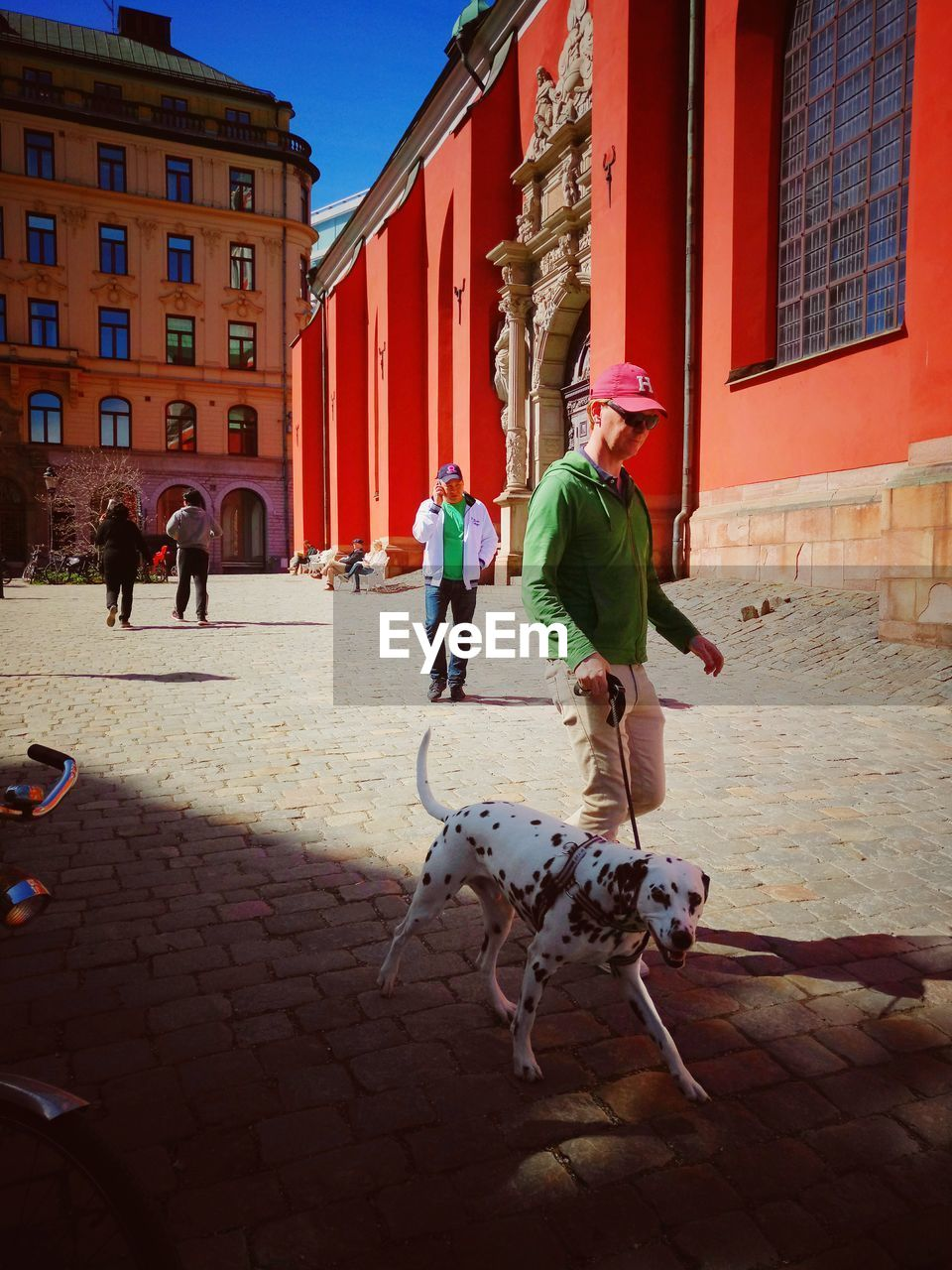 building exterior, real people, architecture, built structure, outdoors, dog, sunlight, day, men, lifestyles, leisure activity, full length, togetherness, pets, mammal, city, people