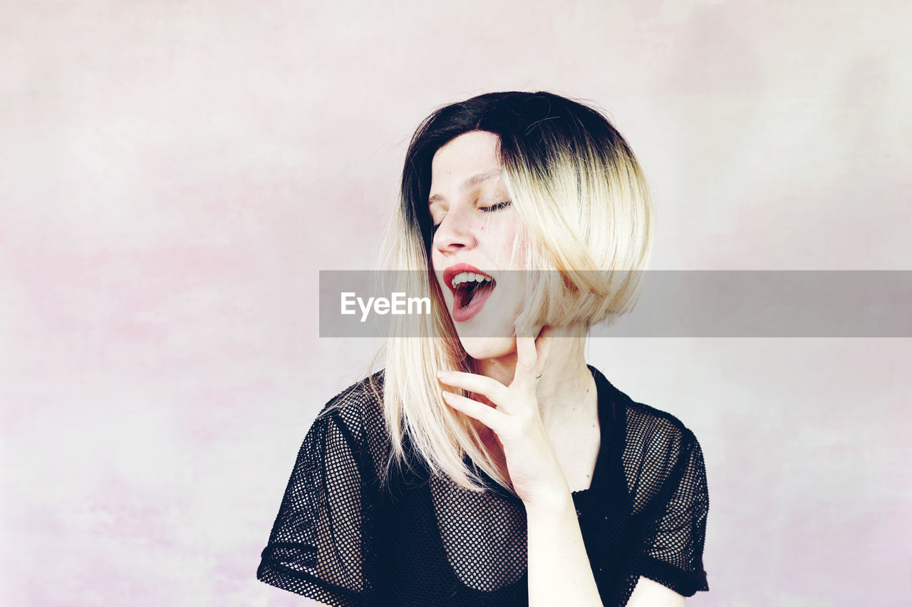 one person, emotion, young adult, mouth, front view, mouth open, indoors, headshot, portrait, young women, hair, studio shot, wall - building feature, shouting, lifestyles, real people, lipstick, standing, hairstyle, beautiful woman, aggression