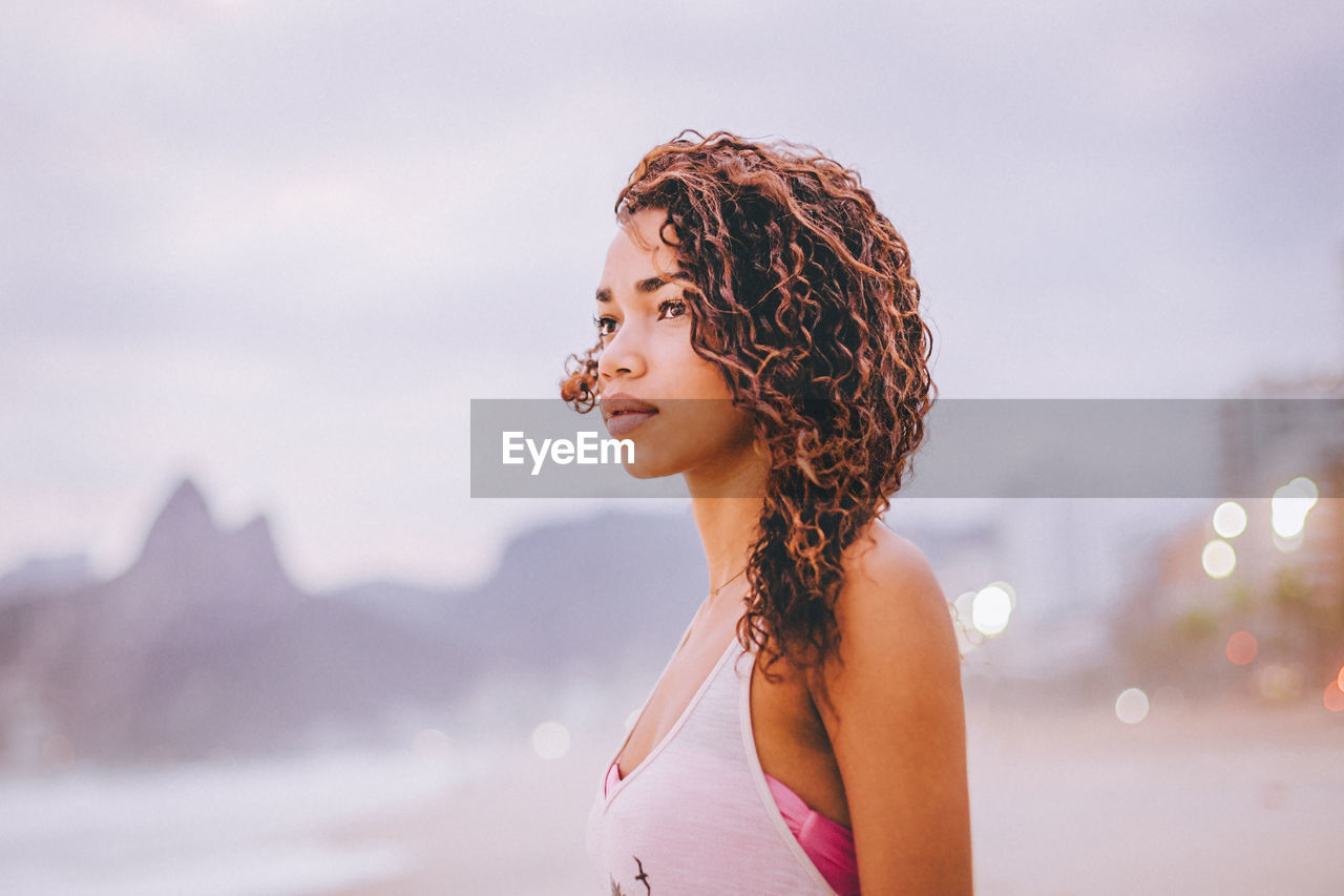 Close-up of young woman looking away at beach during sunset