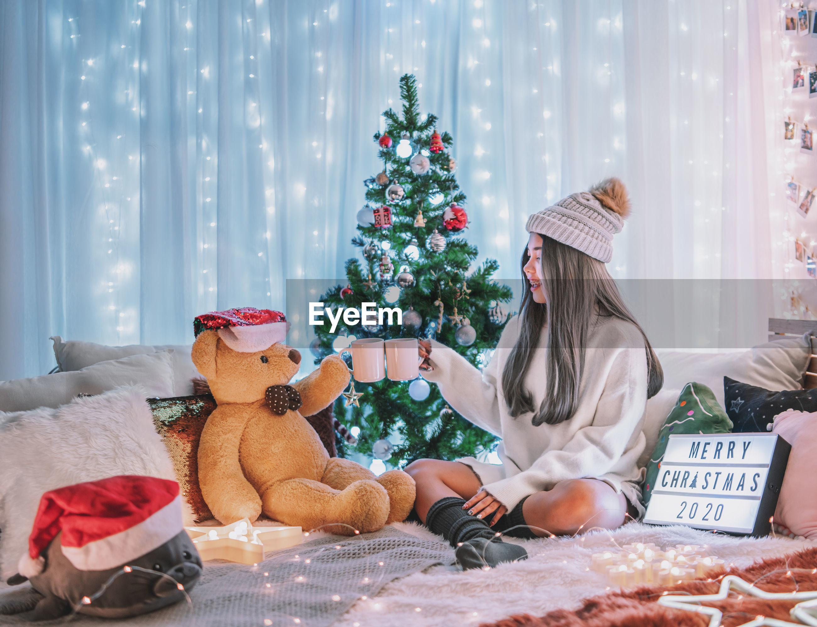 Woman having drink while sitting by teddy bear on bed at home during christmas