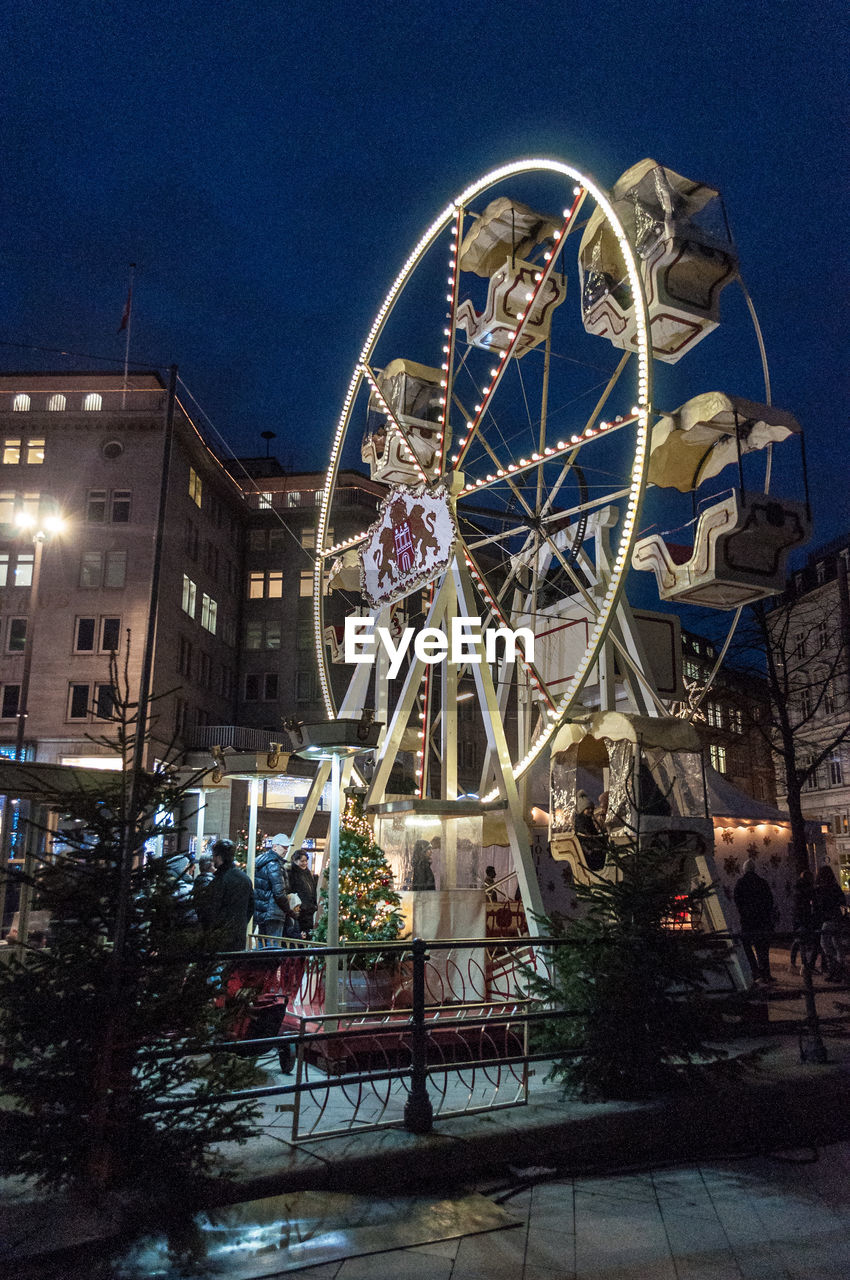 arts culture and entertainment, amusement park, amusement park ride, night, leisure activity, ferris wheel, low angle view, fun, built structure, outdoors, illuminated, sky, building exterior, architecture, no people, carousel