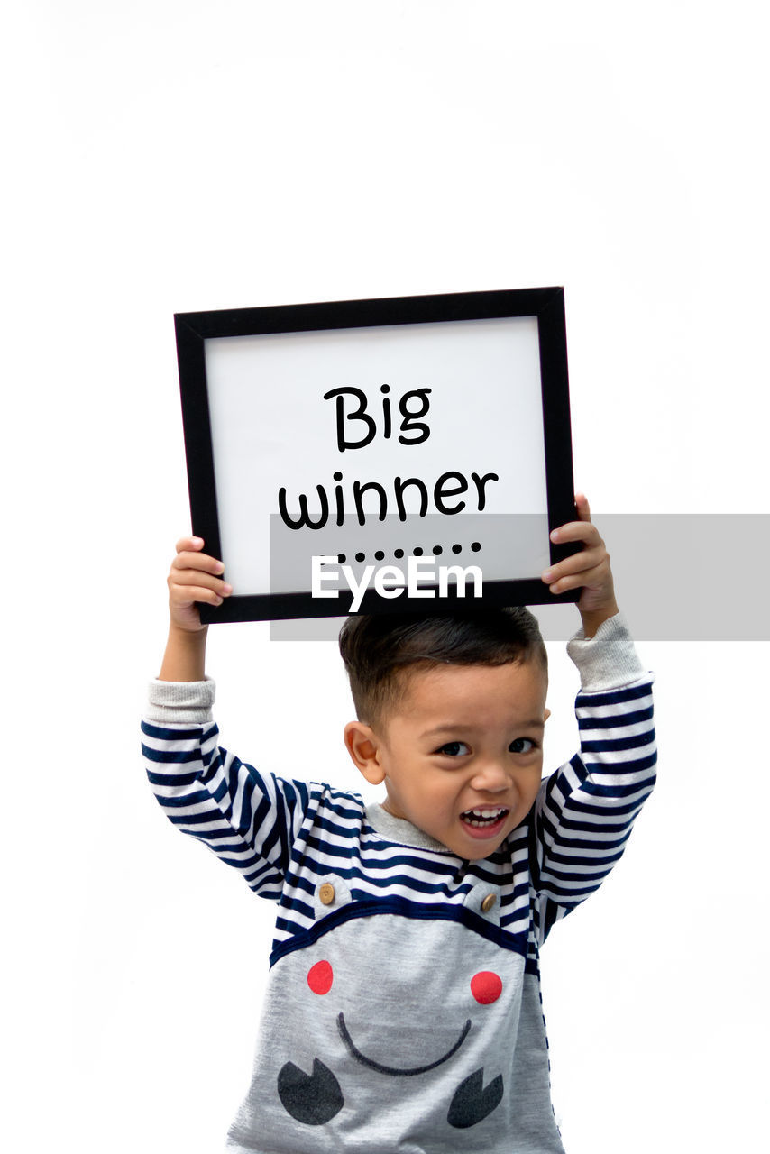 Portrait of boy holding placard with big winner text against white background