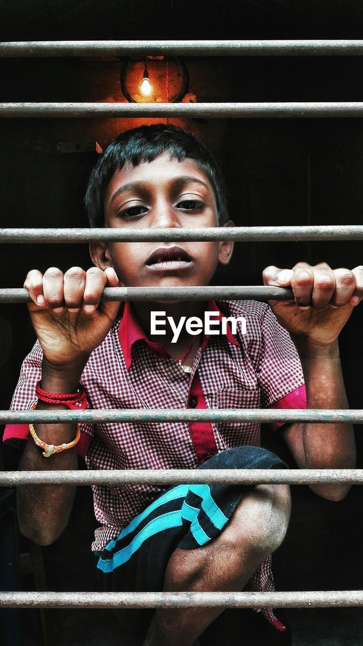 Portrait Of Boy Holding Security Bars On Window
