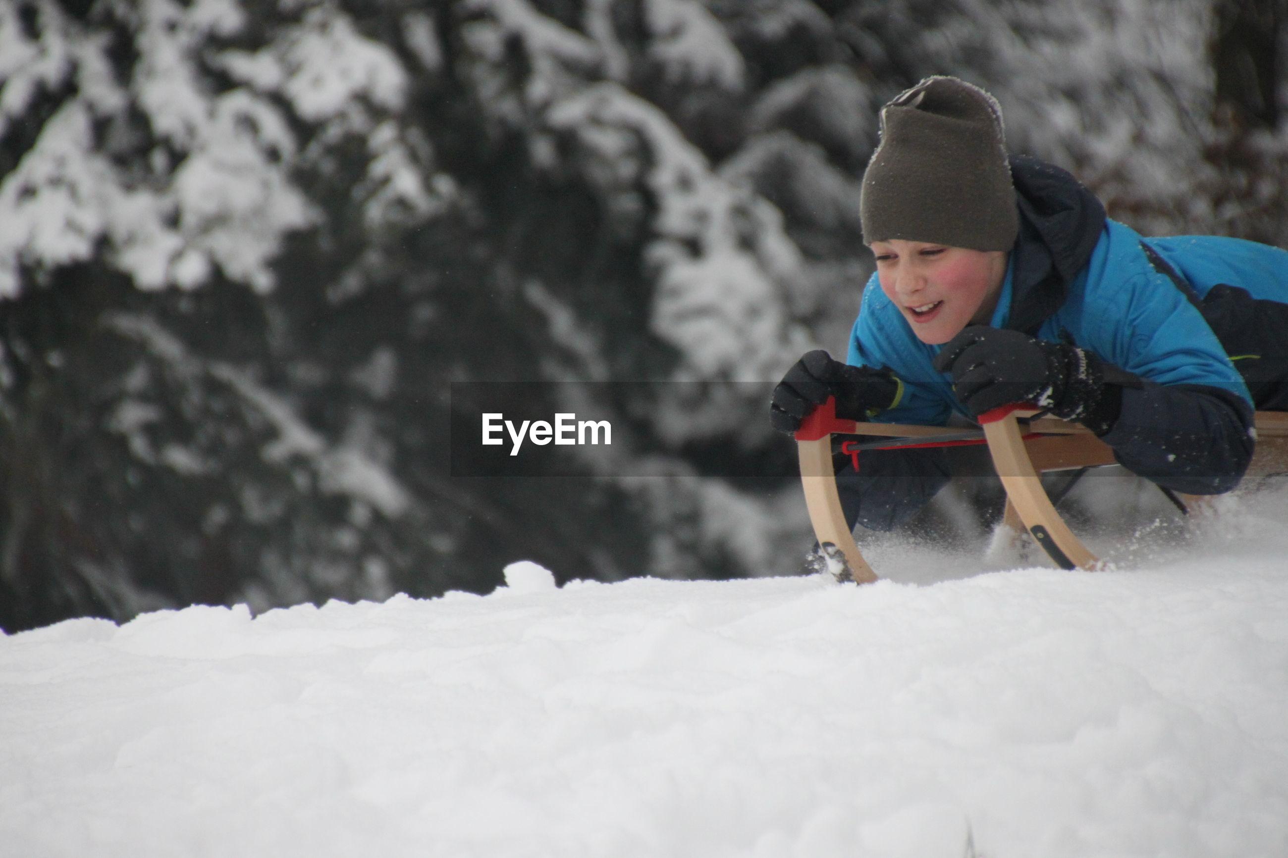 Boy tobogganing on snow covered landscape