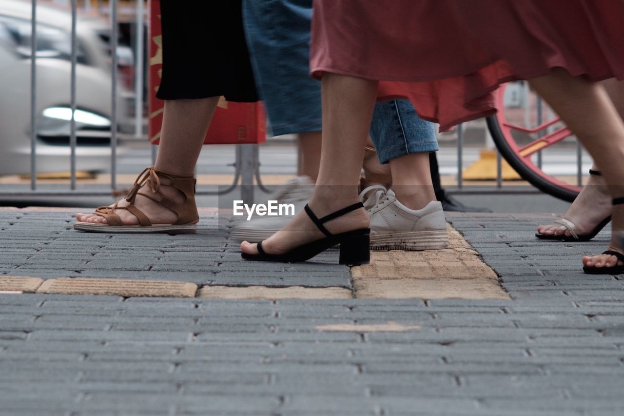 low section, human leg, human body part, body part, women, real people, shoe, group of people, footpath, adult, people, day, sandal, city, lifestyles, street, fashion, standing, leisure activity, human foot, outdoors, human limb, paving stone