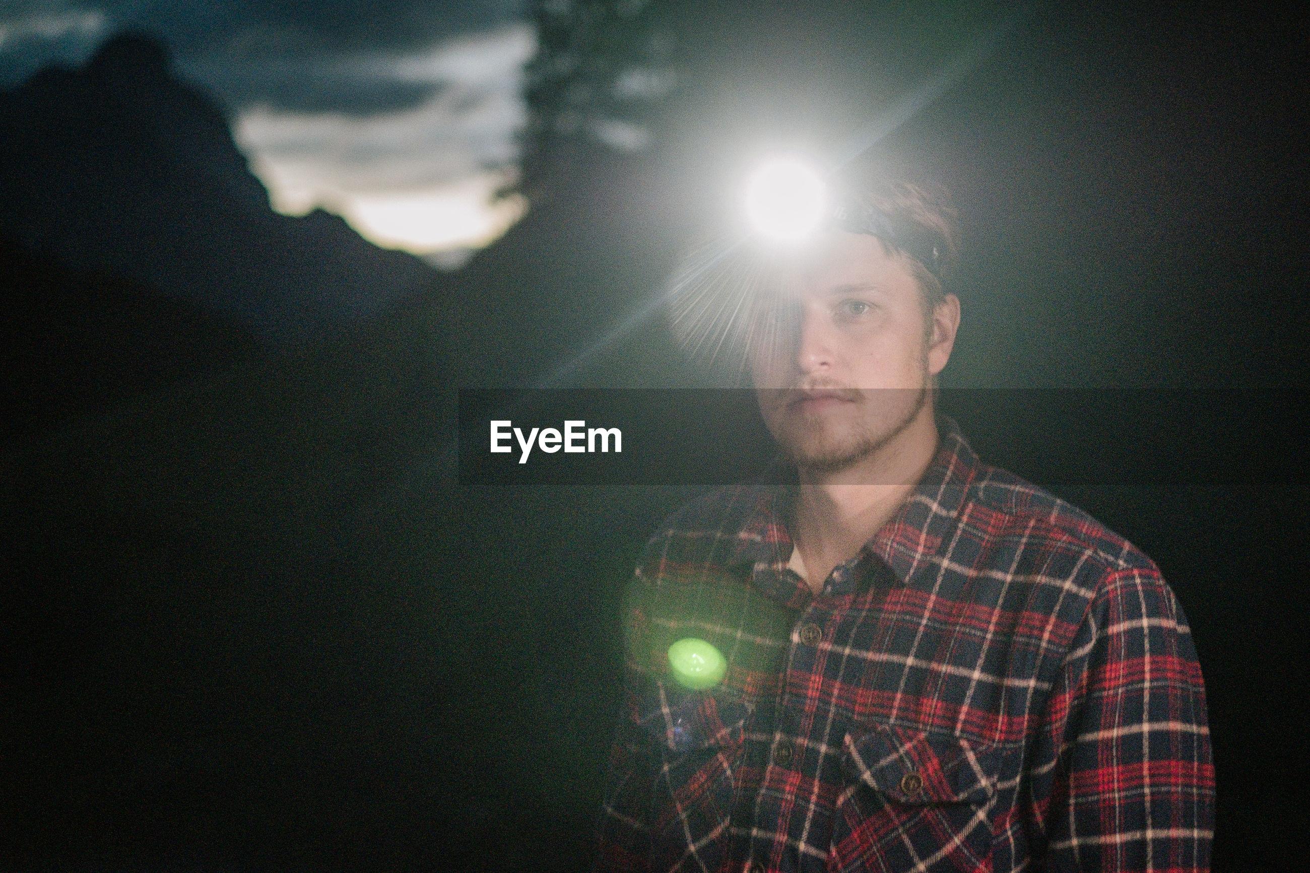 Portrait of man with illuminated lighting equipment at night
