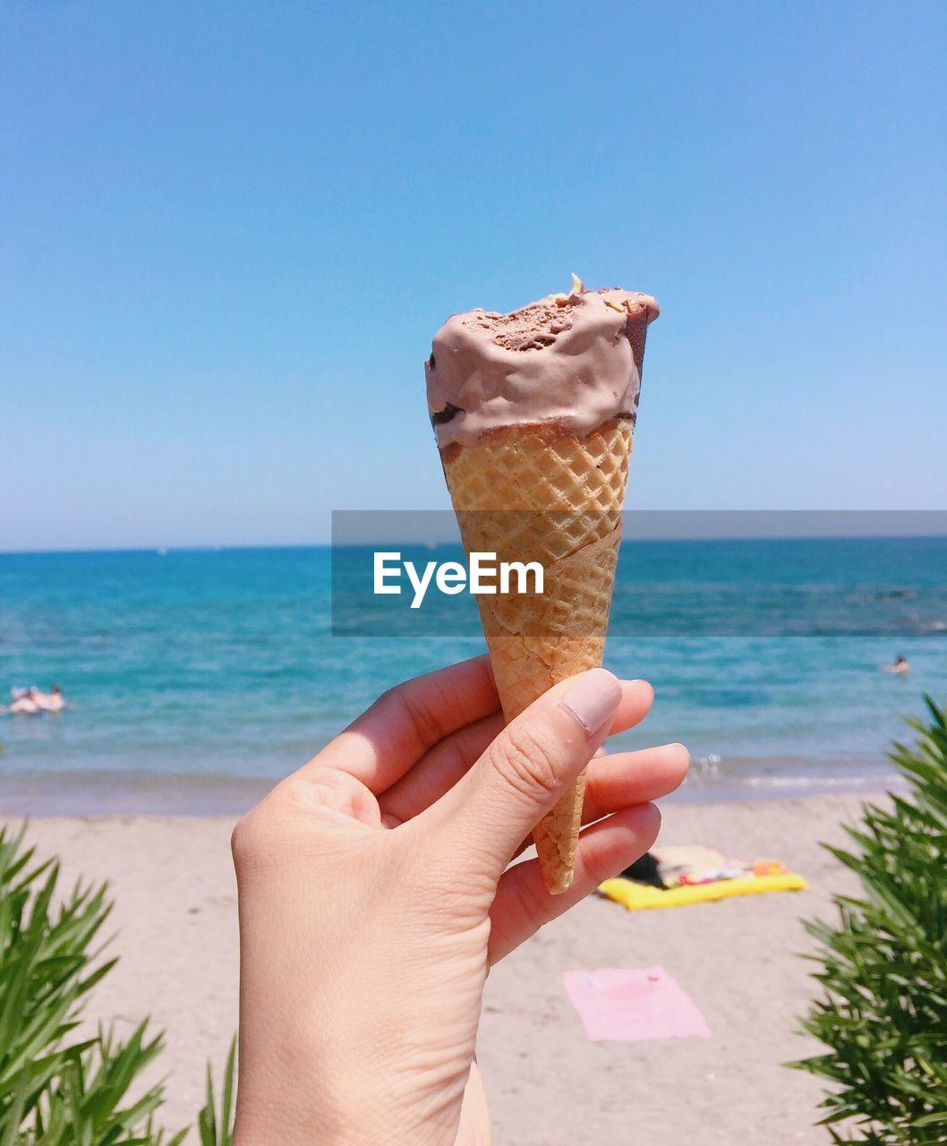 CLOSE-UP OF HAND HOLDING ICE CREAM ON BEACH