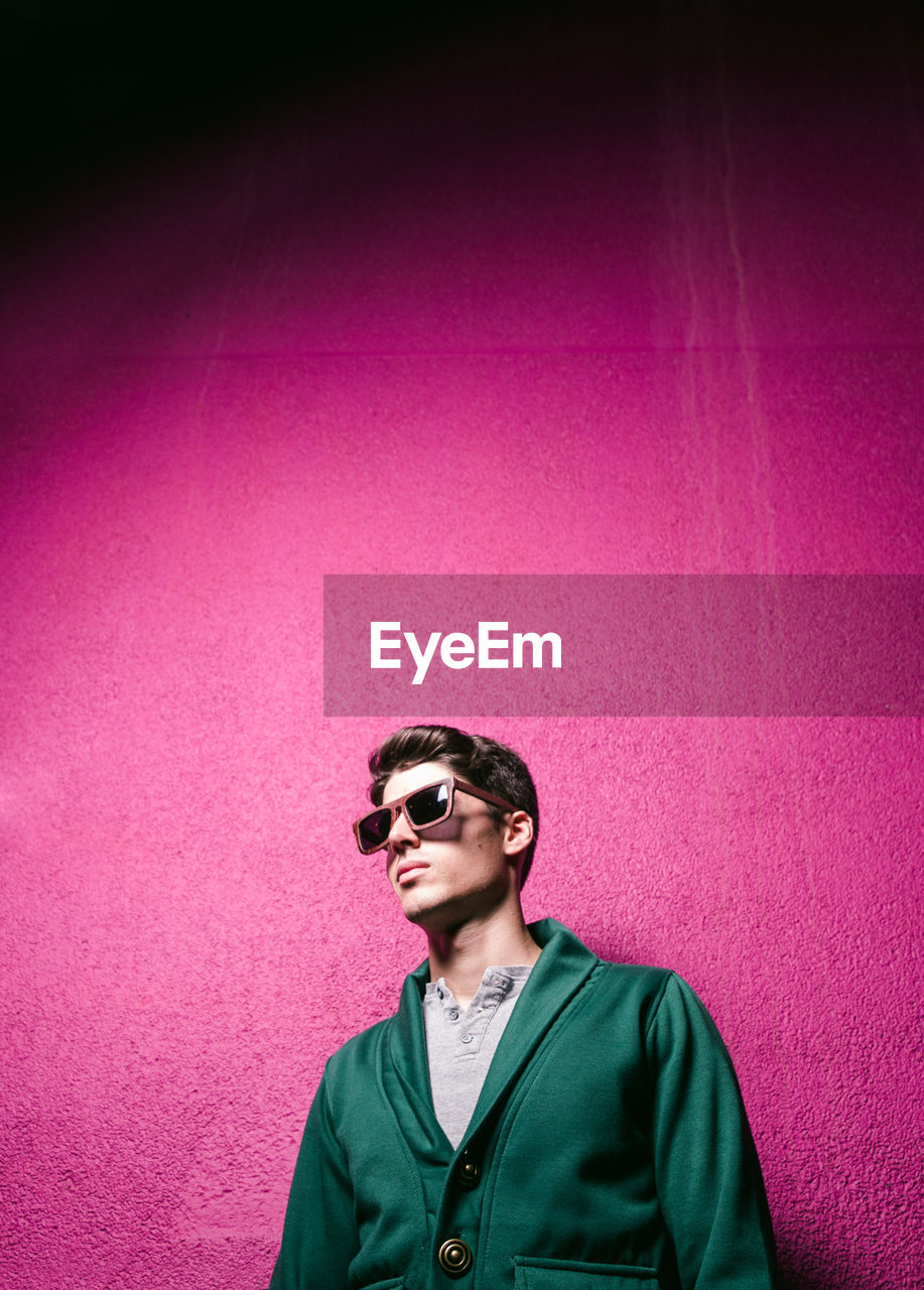 Man Wearing Sunglasses While Standing Against Pink Wall