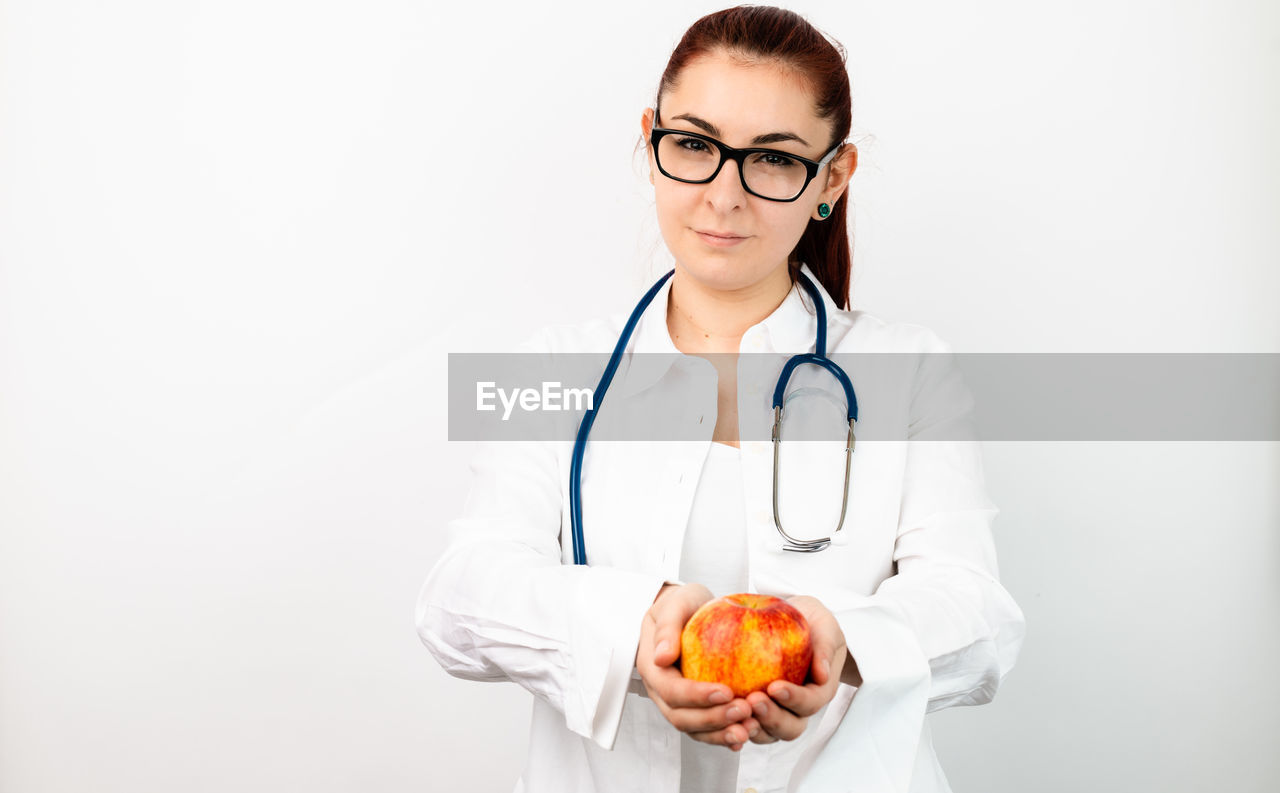medical instrument, doctor, medical equipment, stethoscope, healthcare and medicine, medical supplies, occupation, women, adult, studio shot, standing, indoors, looking at camera, females, eyeglasses, female doctor, portrait, one person, holding, lab coat, care, healthcare worker, uniform