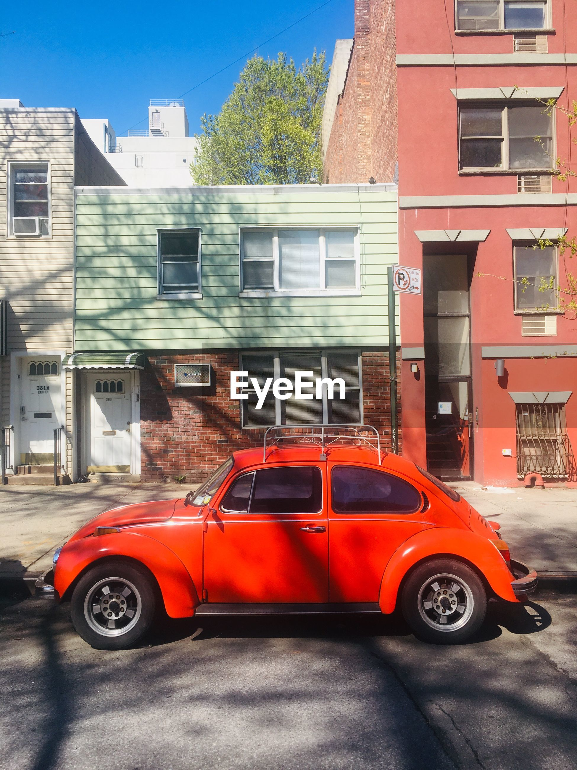 RED CAR ON STREET AGAINST BUILDINGS