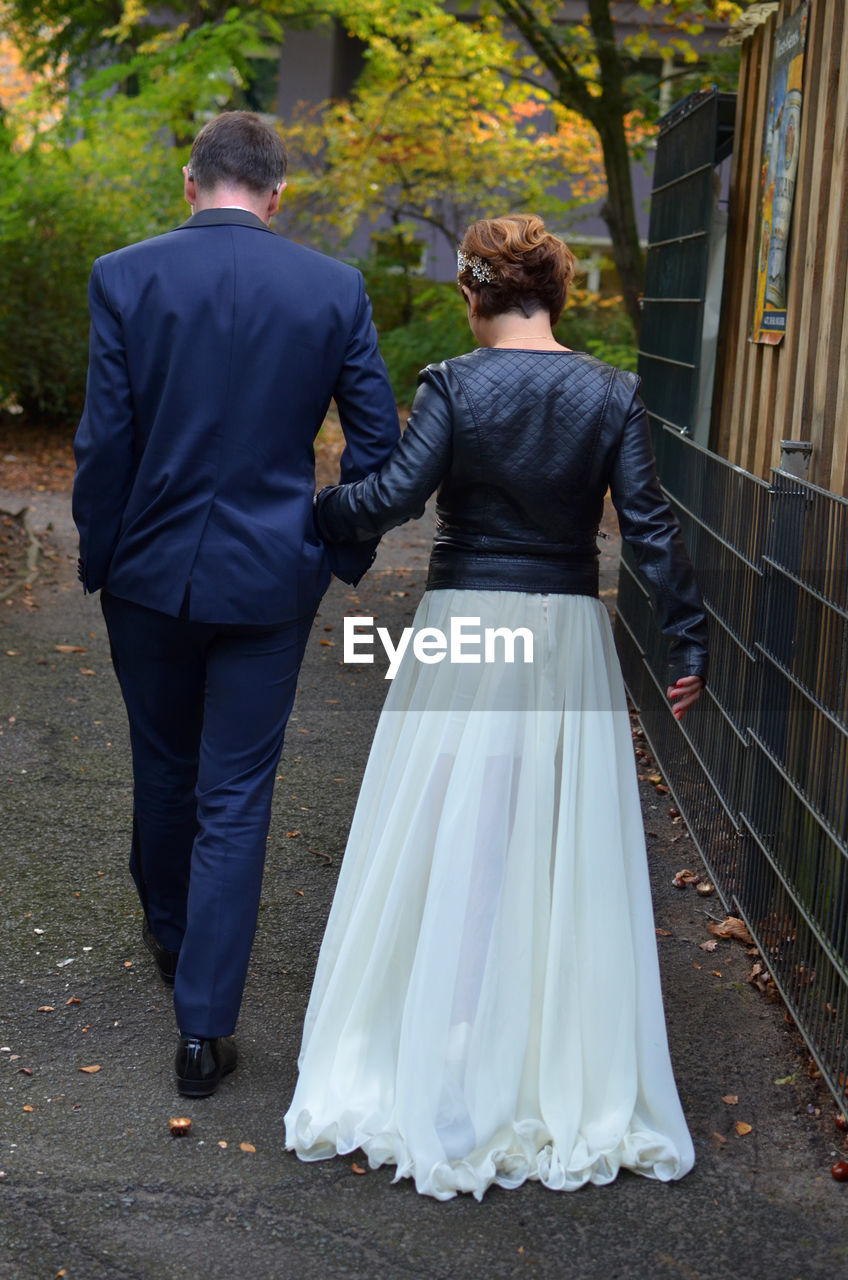 rear view, two people, wedding, love, togetherness, real people, full length, bride, men, bridegroom, heterosexual couple, celebration, women, husband, groom, life events, walking, wife, couple - relationship, well-dressed, bonding, day, wedding dress, outdoors, lifestyles, tree, ceremony, married