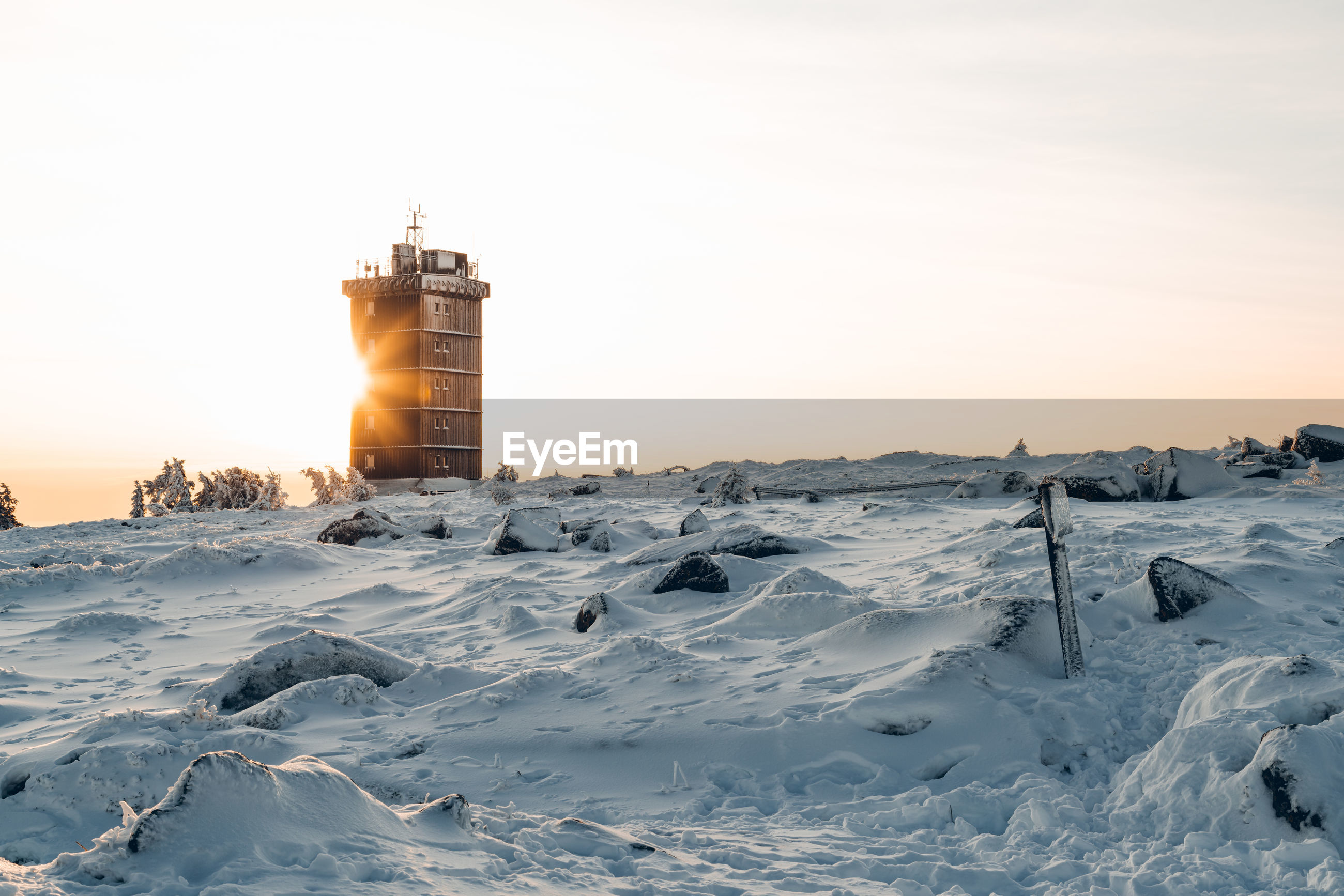 Lighthouse on snow covered building against sky during sunset