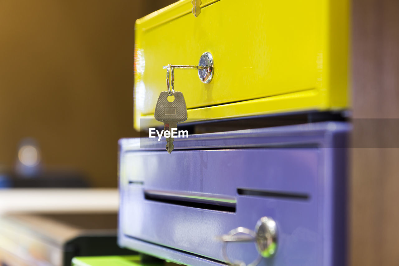 selective focus, yellow, no people, metal, indoors, close-up, blue, technology, still life, communication, equipment, mailbox, security, knob, focus on foreground, drawer, public mailbox, mail, wood - material
