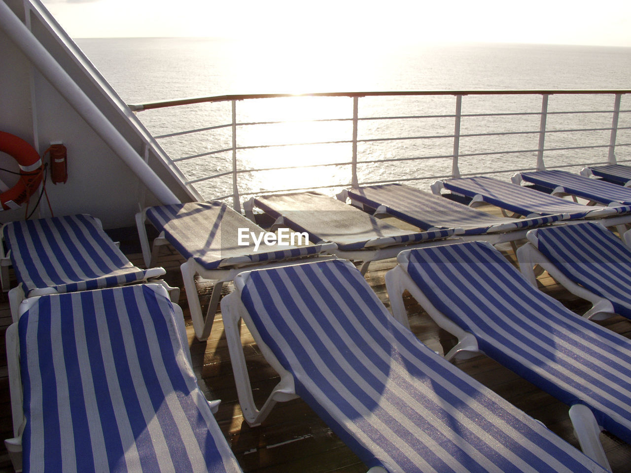 Lounge chairs on boat deck in sea