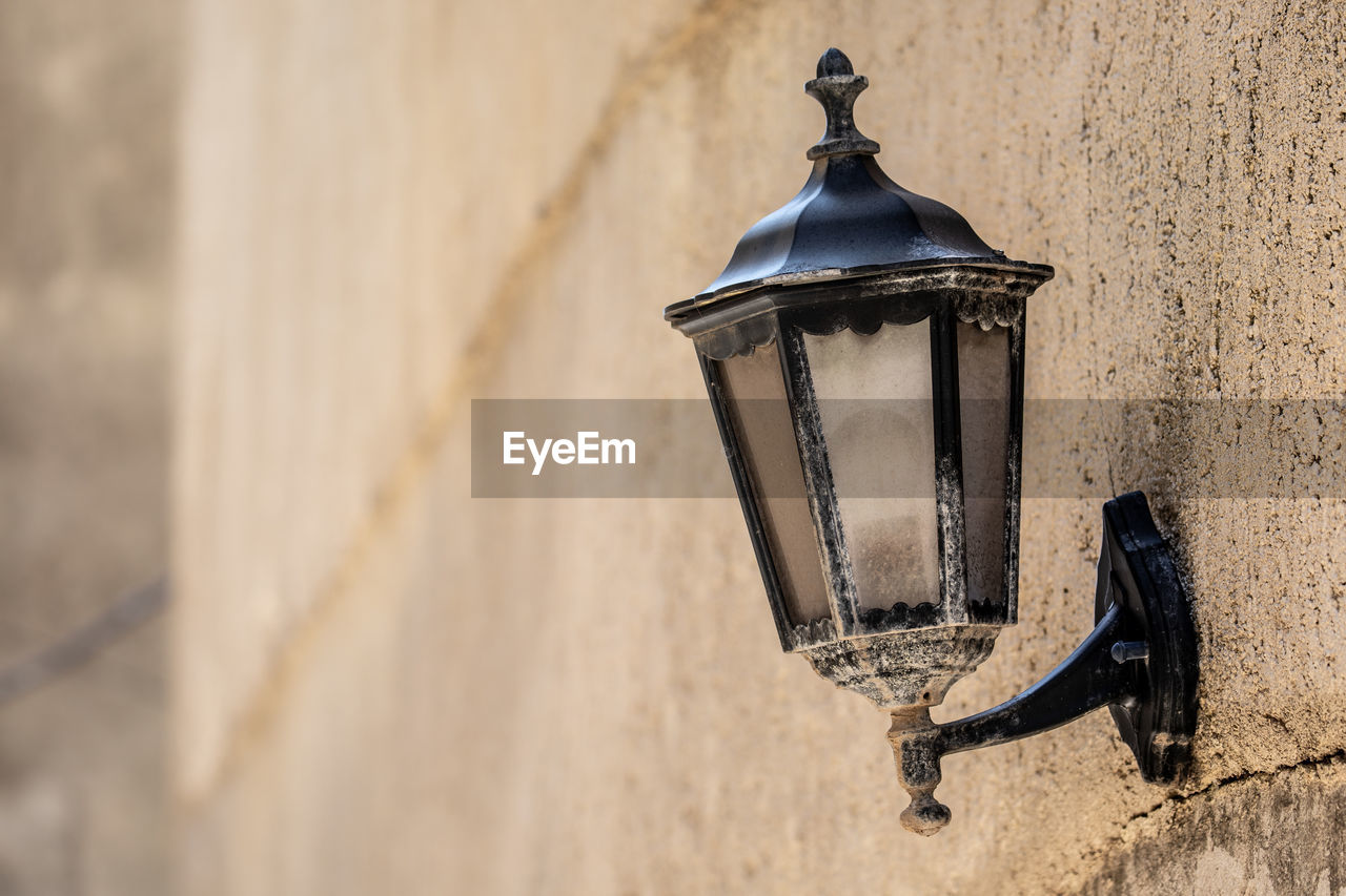 wall - building feature, lighting equipment, metal, no people, focus on foreground, built structure, architecture, day, close-up, building exterior, old, electric lamp, wall, hanging, outdoors, absence, building, lantern, nature