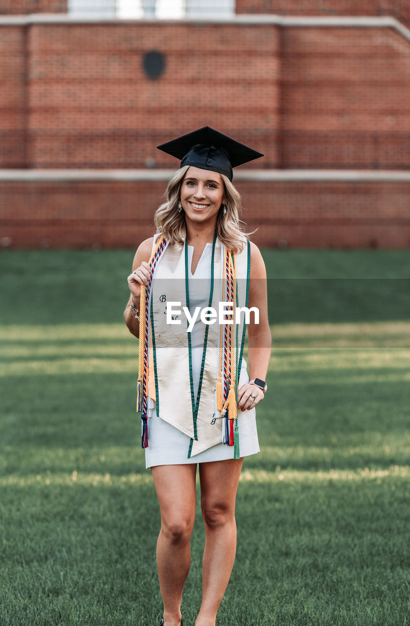 Full length of smiling woman standing on grass at park