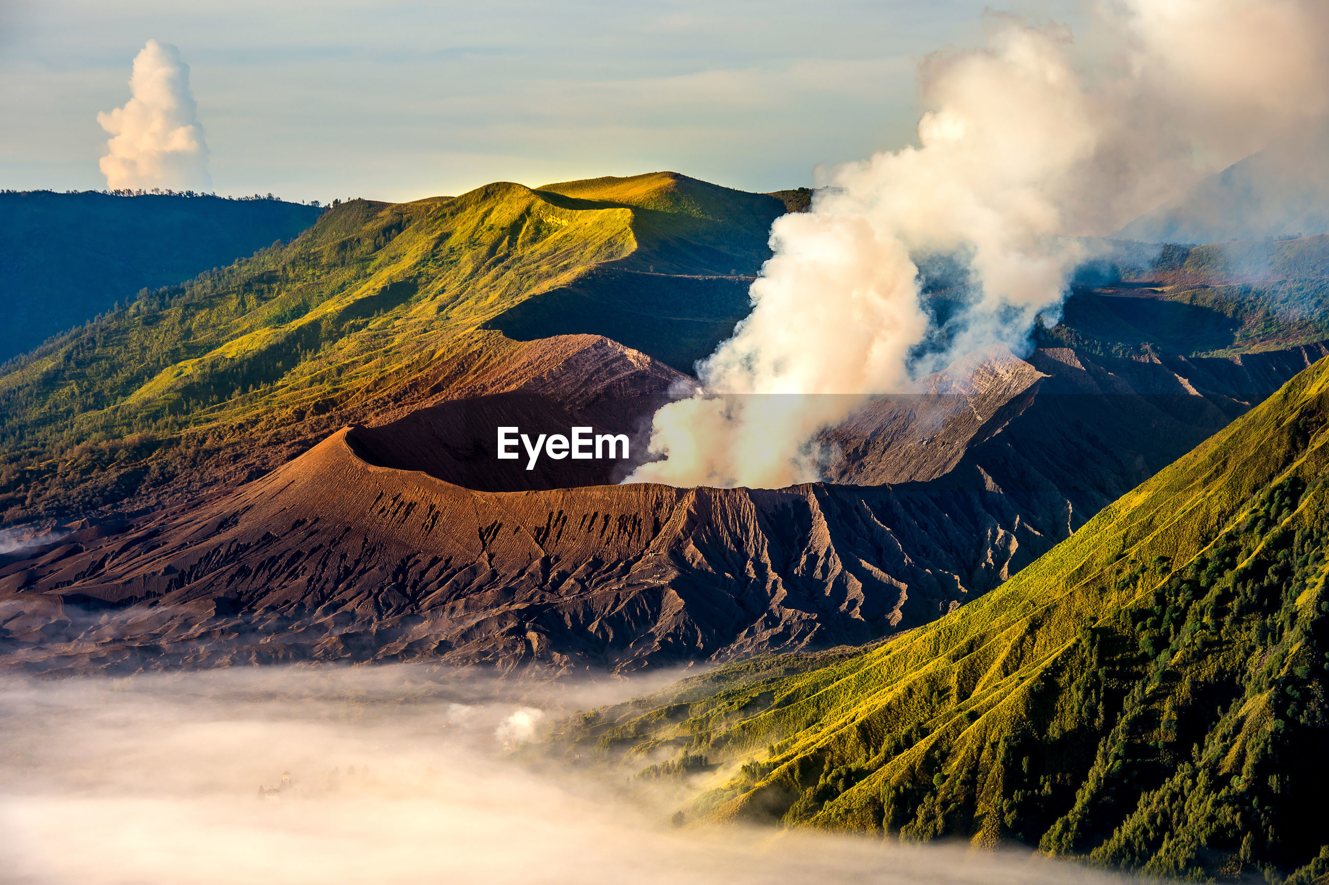 Active volcano at bromo crater against sky during sunrise