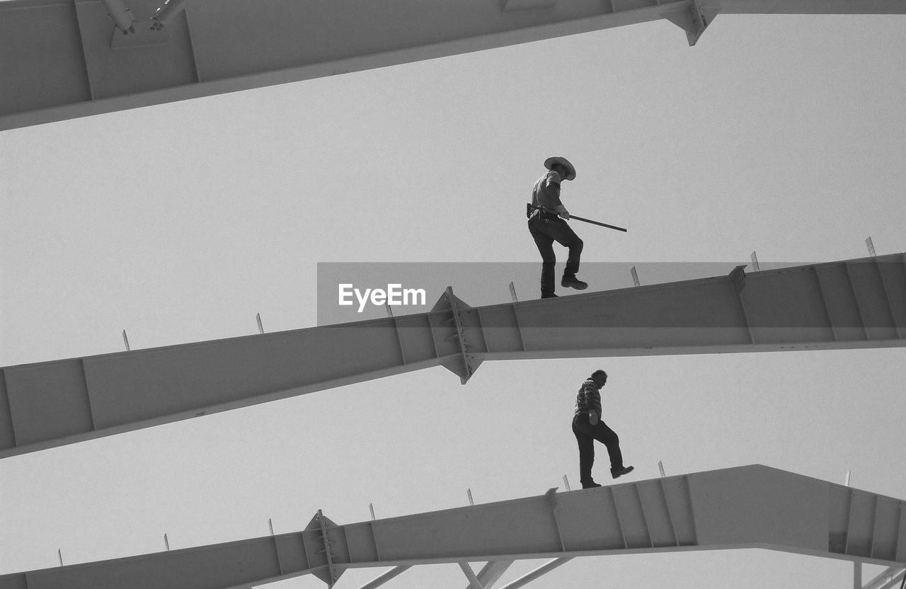 Low Angle View Of Manual Workers Walking On Steel Structure