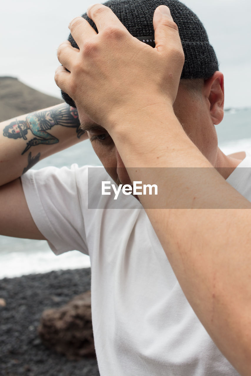 real people, one person, lifestyles, hand, leisure activity, human hand, tattoo, focus on foreground, human body part, men, day, land, beach, body part, casual clothing, adult, close-up, young adult, young men, outdoors