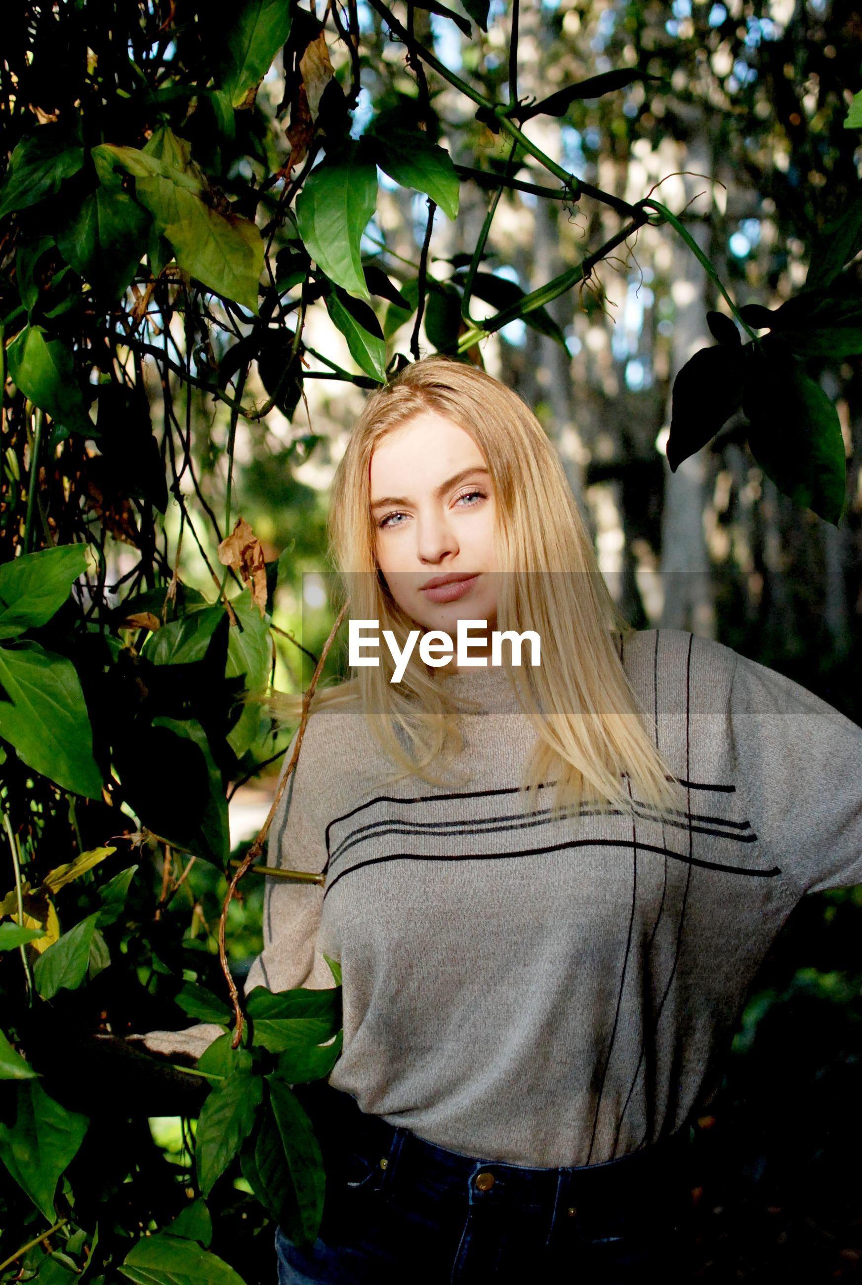 Portrait of confident young woman standing amidst plants at public park