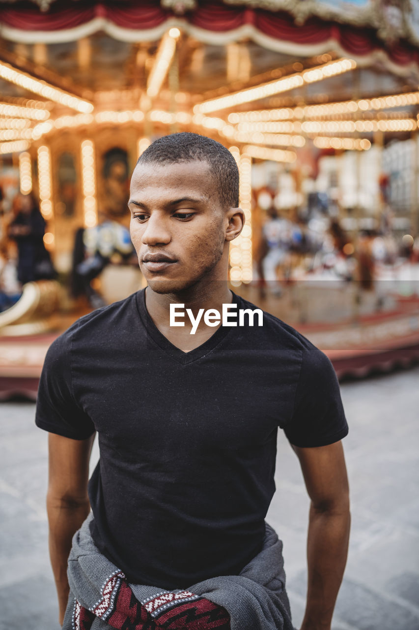 one person, front view, leisure activity, young men, lifestyles, three quarter length, young adult, focus on foreground, real people, casual clothing, portrait, looking at camera, men, amusement park ride, adult, looking, waist up, amusement park, arts culture and entertainment
