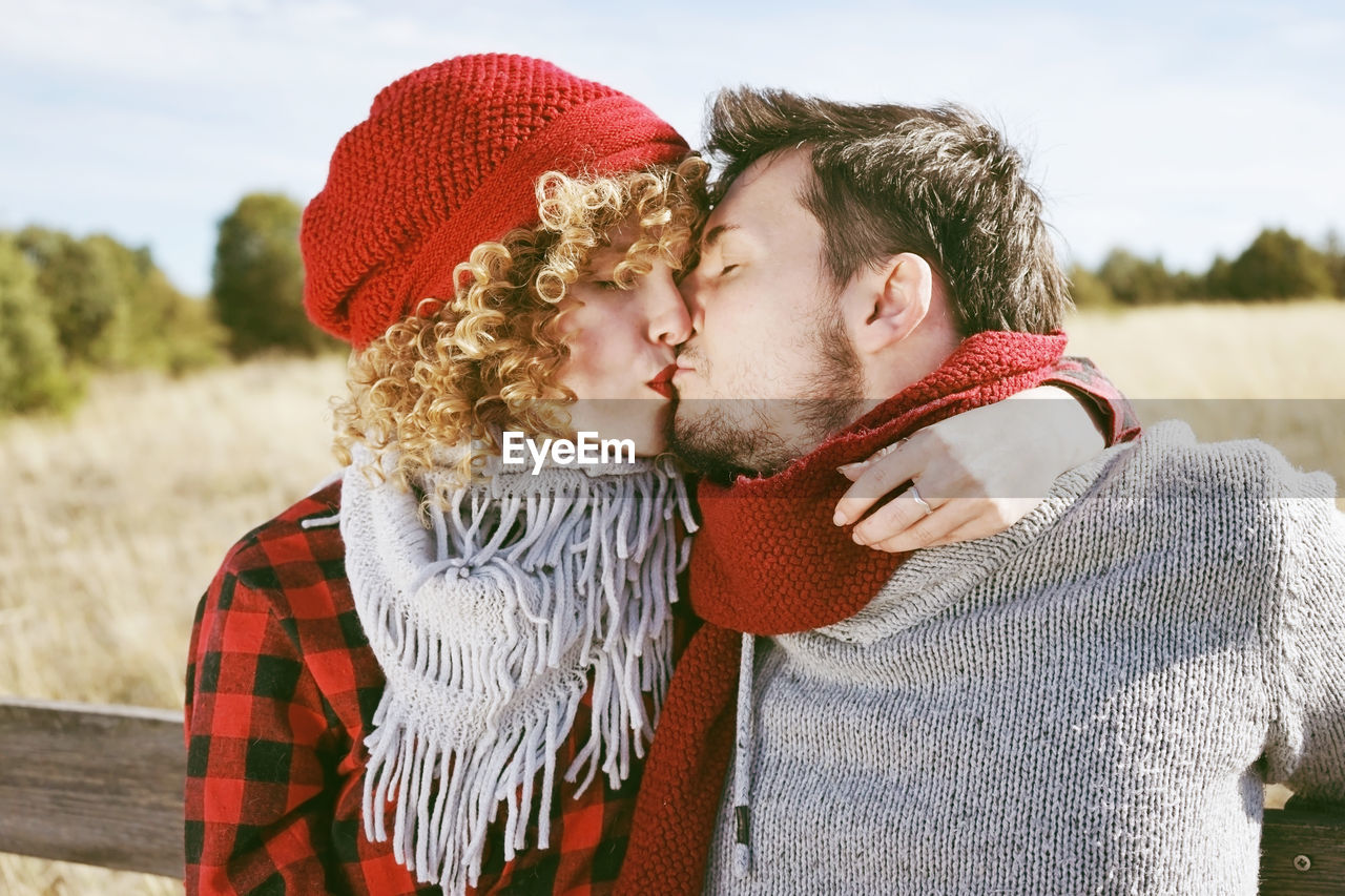 Couple wearing warm clothing kissing on mouth in park