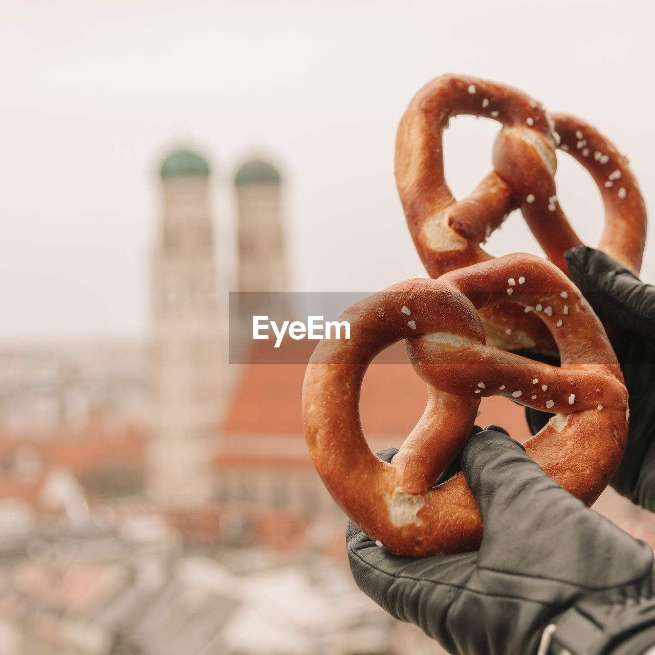 Close-up of person holding pretzel in city