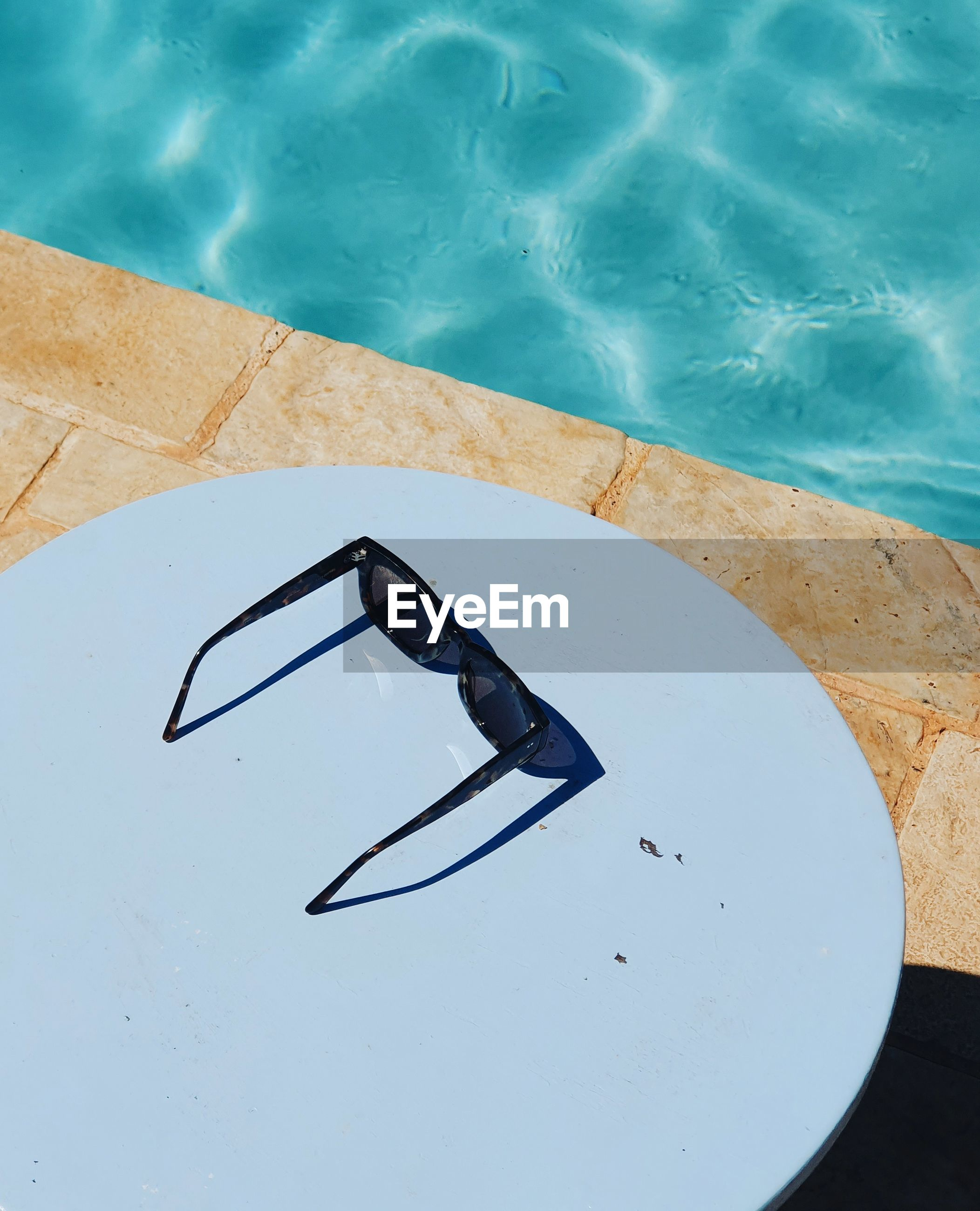 High angle view of sunglasses by swimming pool