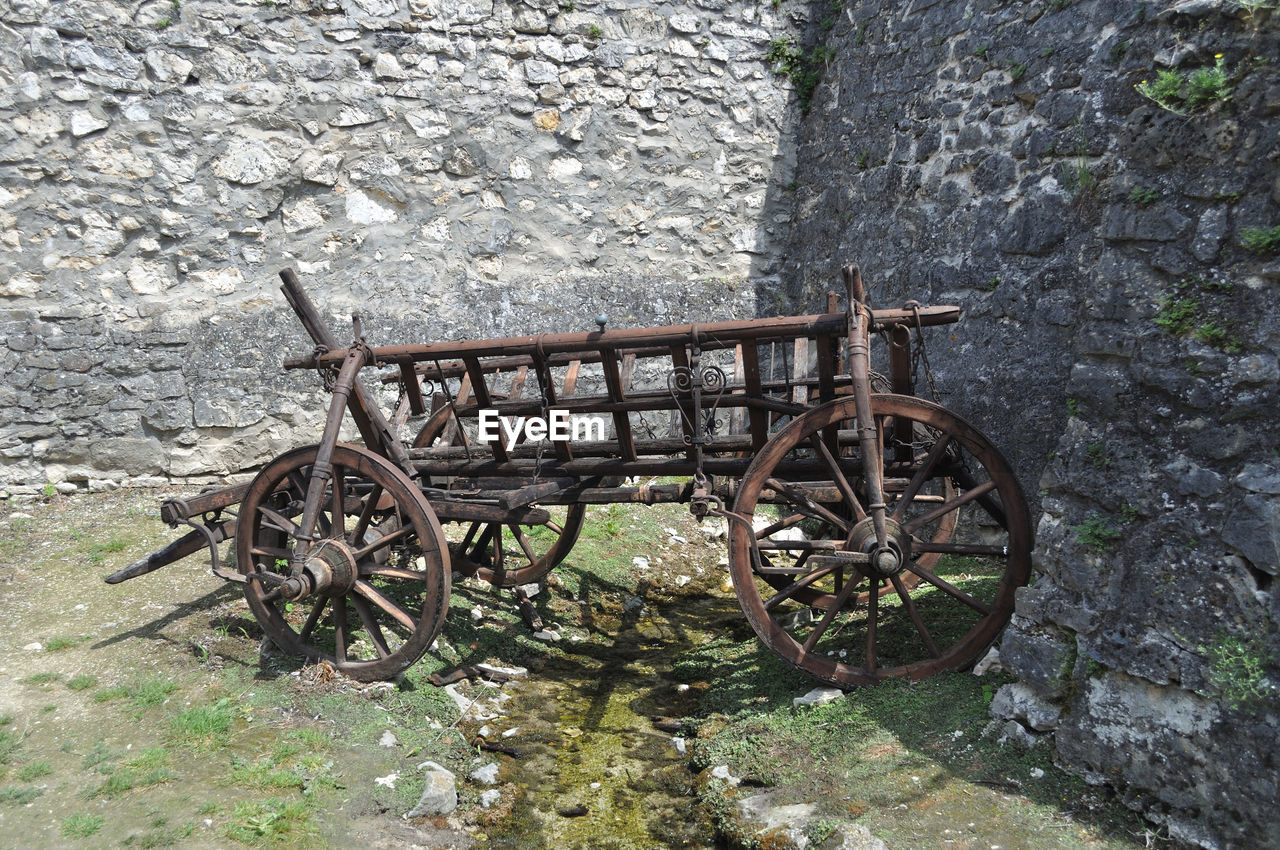 day, no people, stone wall, wheel, old, wall, transportation, wall - building feature, cart, abandoned, run-down, nature, outdoors, damaged, built structure, obsolete, architecture, metal, wood - material, weathered, deterioration, wagon wheel