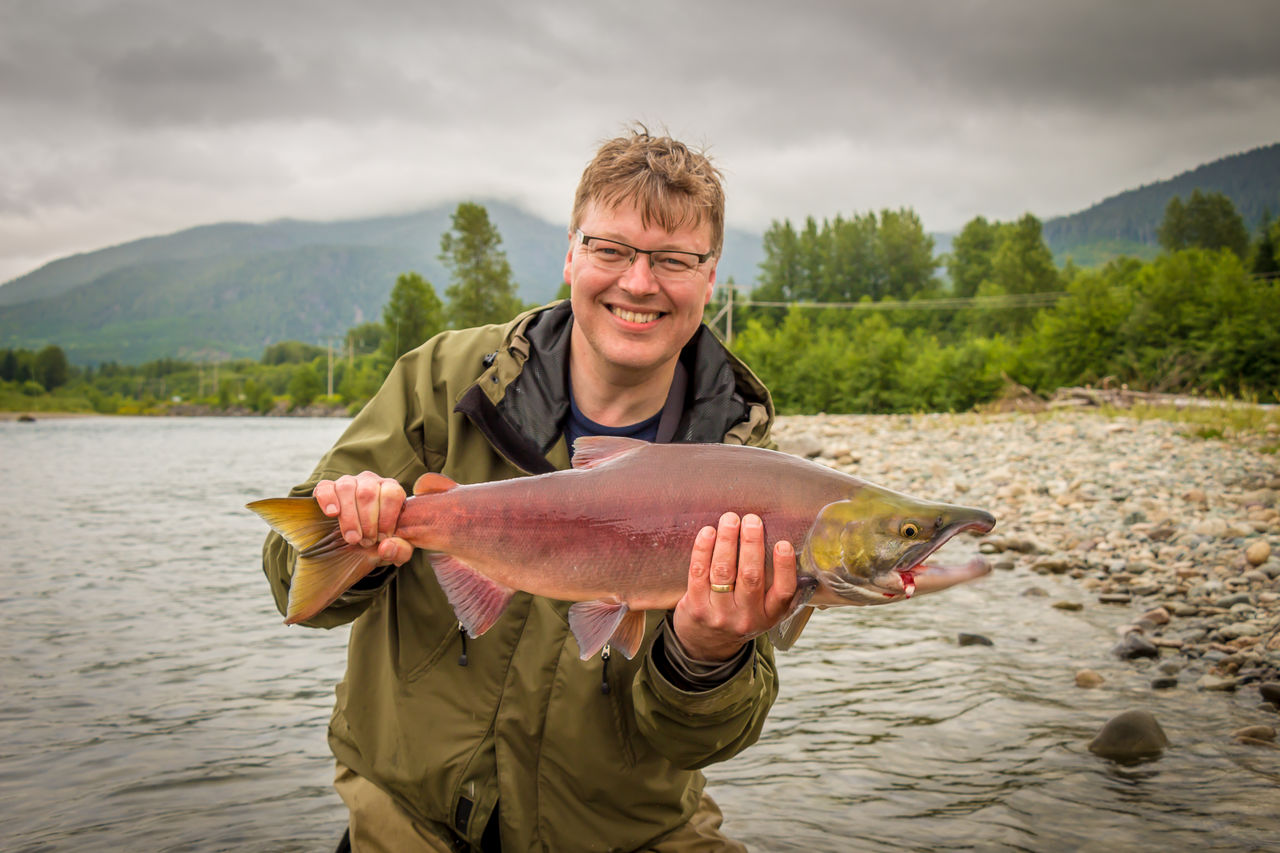 Portrait of mature man holding fish standing by river against sky
