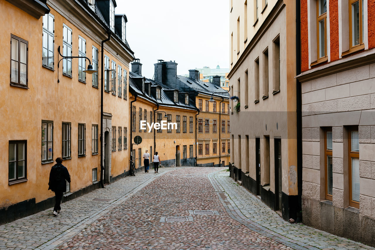 Traditional residential house in stockholm. yellow painted facade against sky.