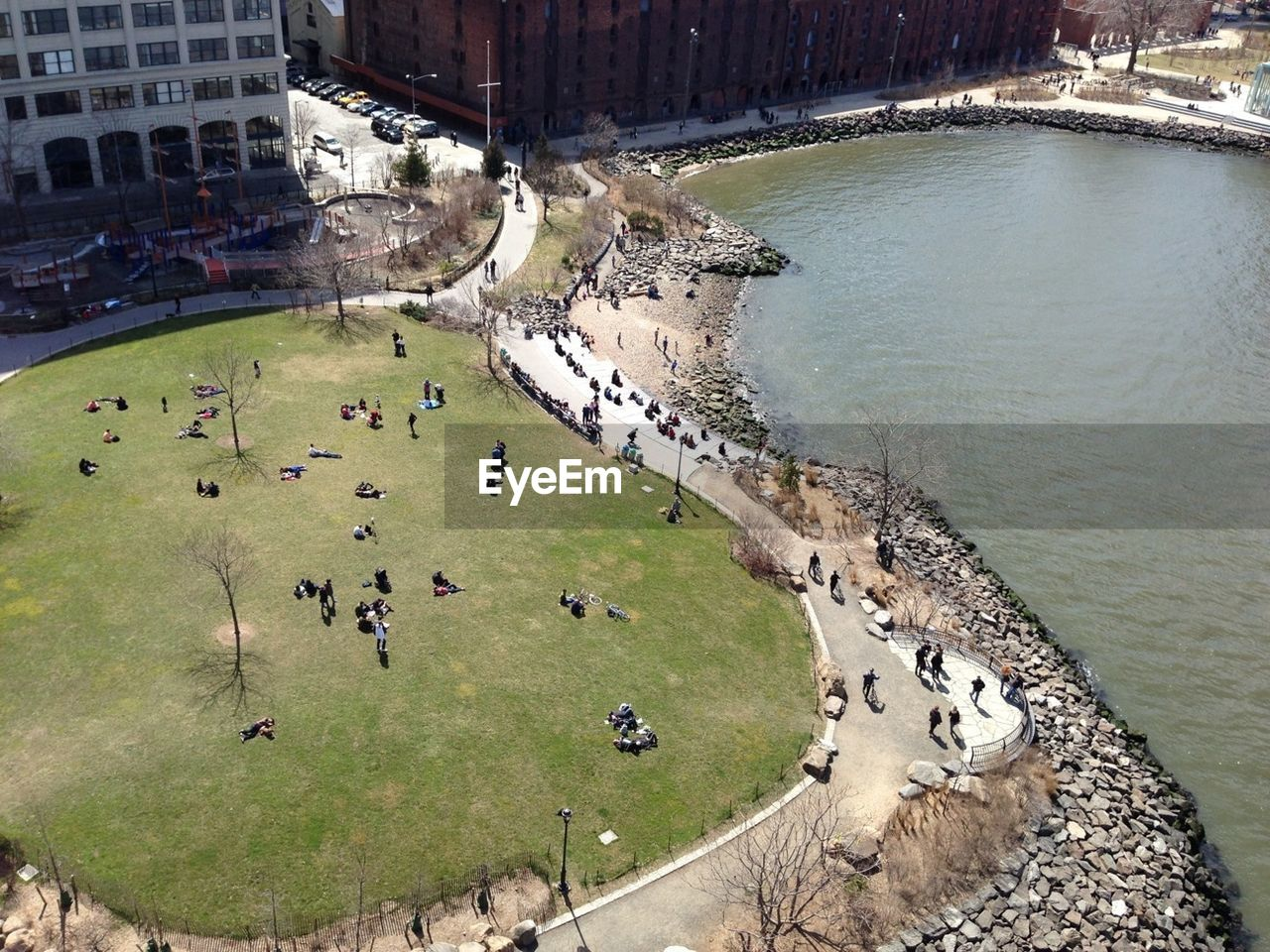 High angle view of people sitting on grass by the lake