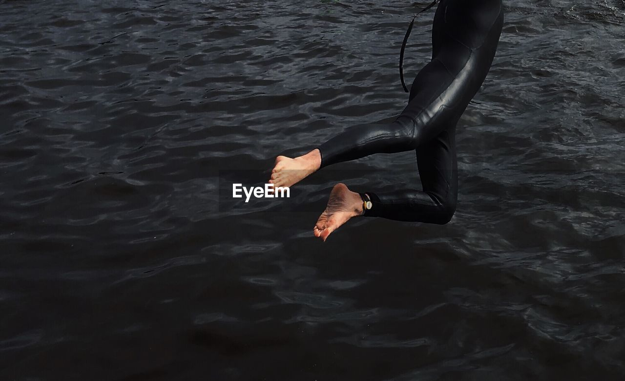 Low Section Of Person Jumping In Sea