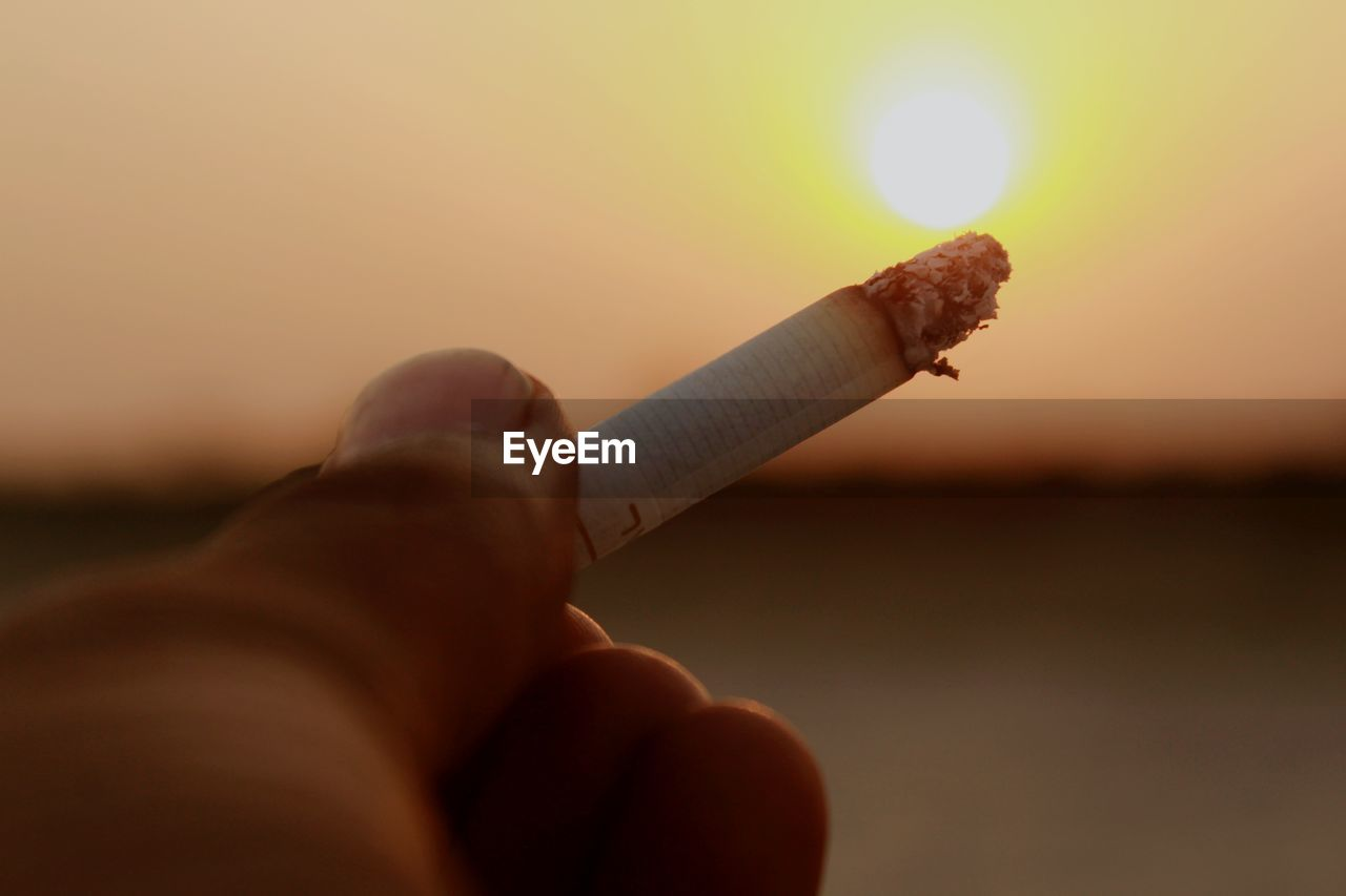 human hand, hand, holding, one person, human body part, real people, personal perspective, bad habit, smoking issues, finger, cigarette, lifestyles, unrecognizable person, human finger, focus on foreground, social issues, sky, sunset, body part, outdoors