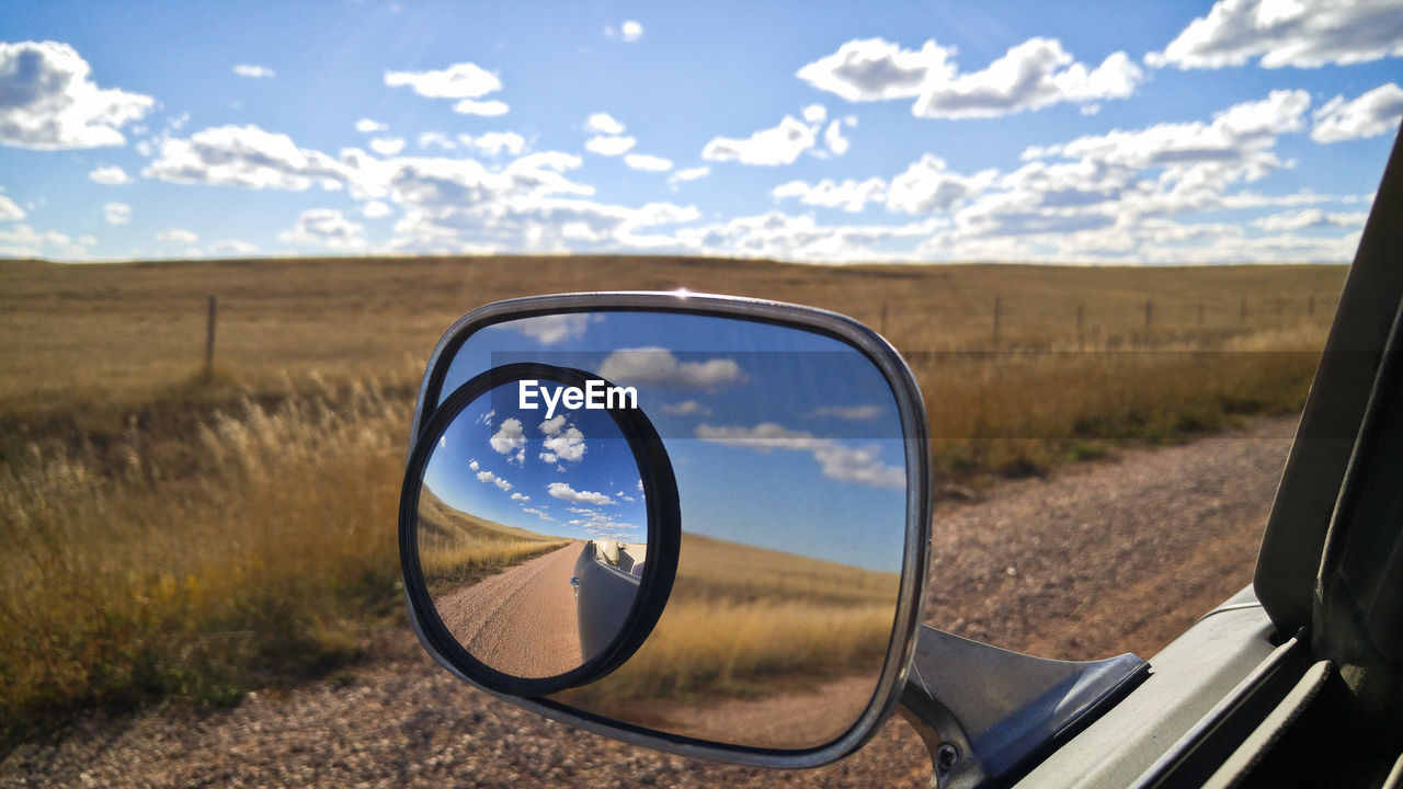 sky, land, cloud - sky, landscape, nature, side-view mirror, motor vehicle, car, field, land vehicle, reflection, scenics - nature, transportation, environment, glass - material, day, mirror, transparent, road, outdoors, vehicle mirror, no people