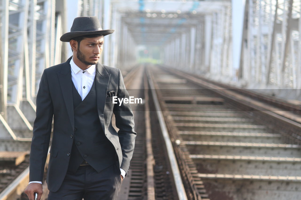 Man in suit looking away while standing at railway bridge