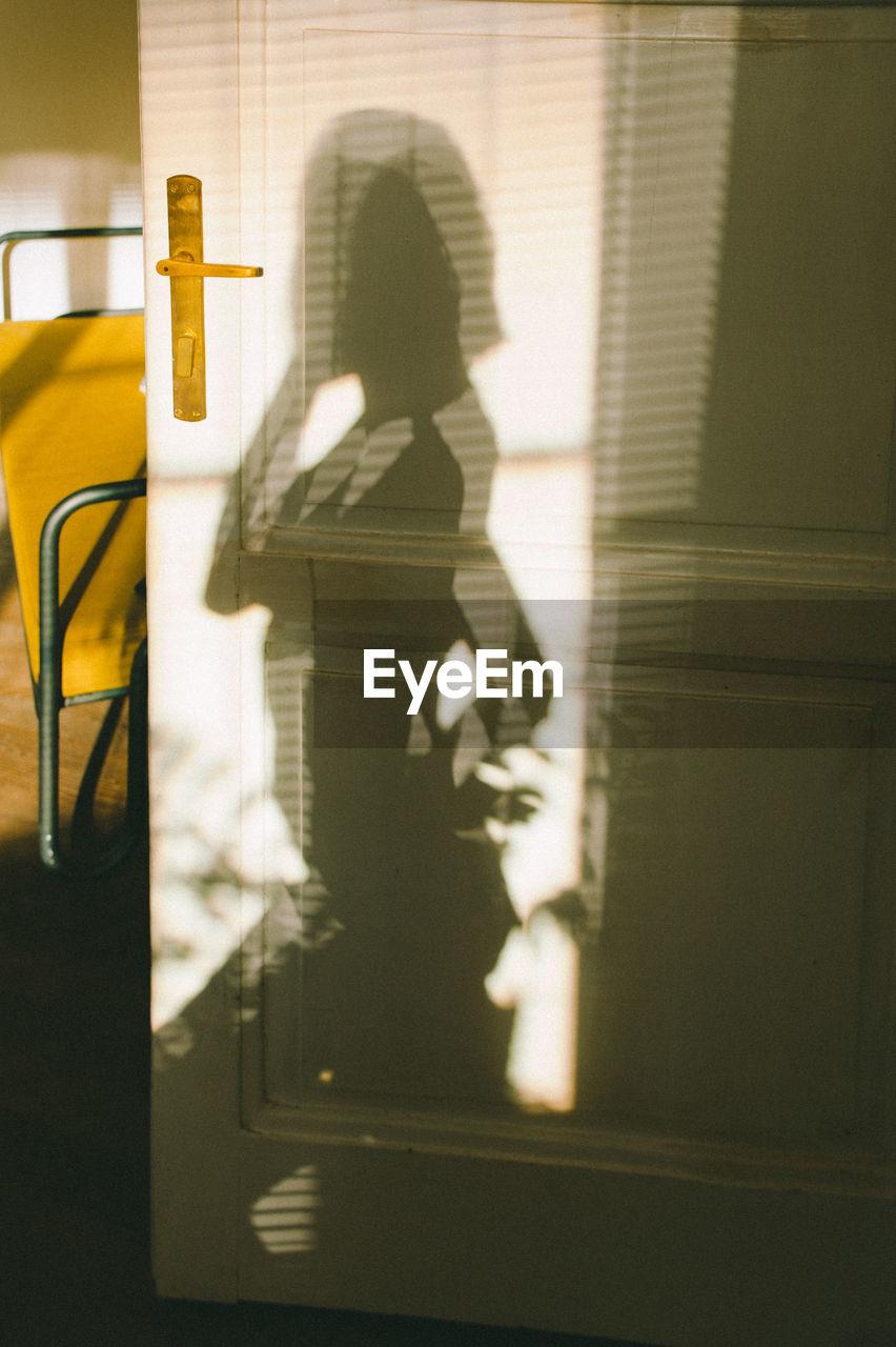 Shadow of man and woman walking on yellow door
