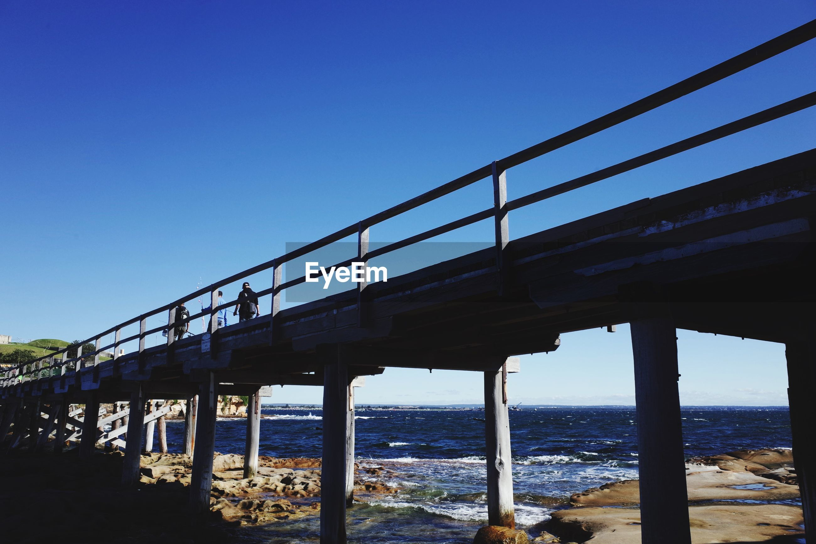 clear sky, water, connection, sea, bridge - man made structure, built structure, bridge, railing, copy space, blue, transportation, engineering, architecture, horizon over water, sky, tranquility, outdoors, day, tranquil scene, nature