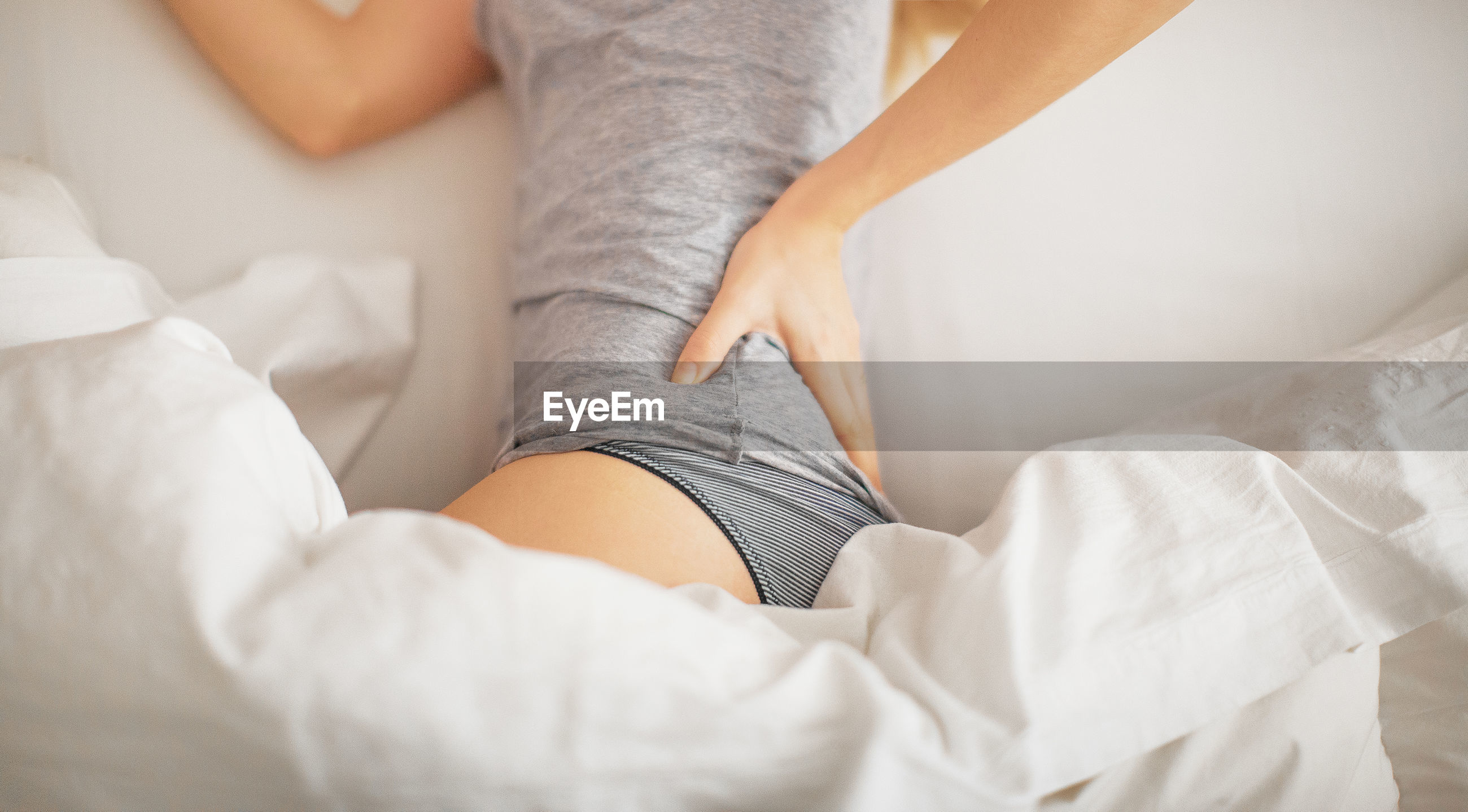 Midsection of young woman with back pain lying on bed at home