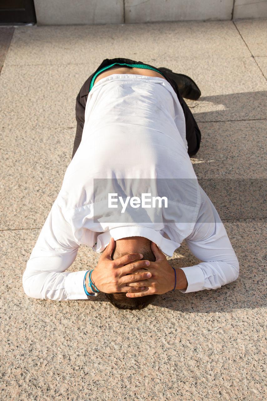 High Angle View Of Businessman Kneeling On Street